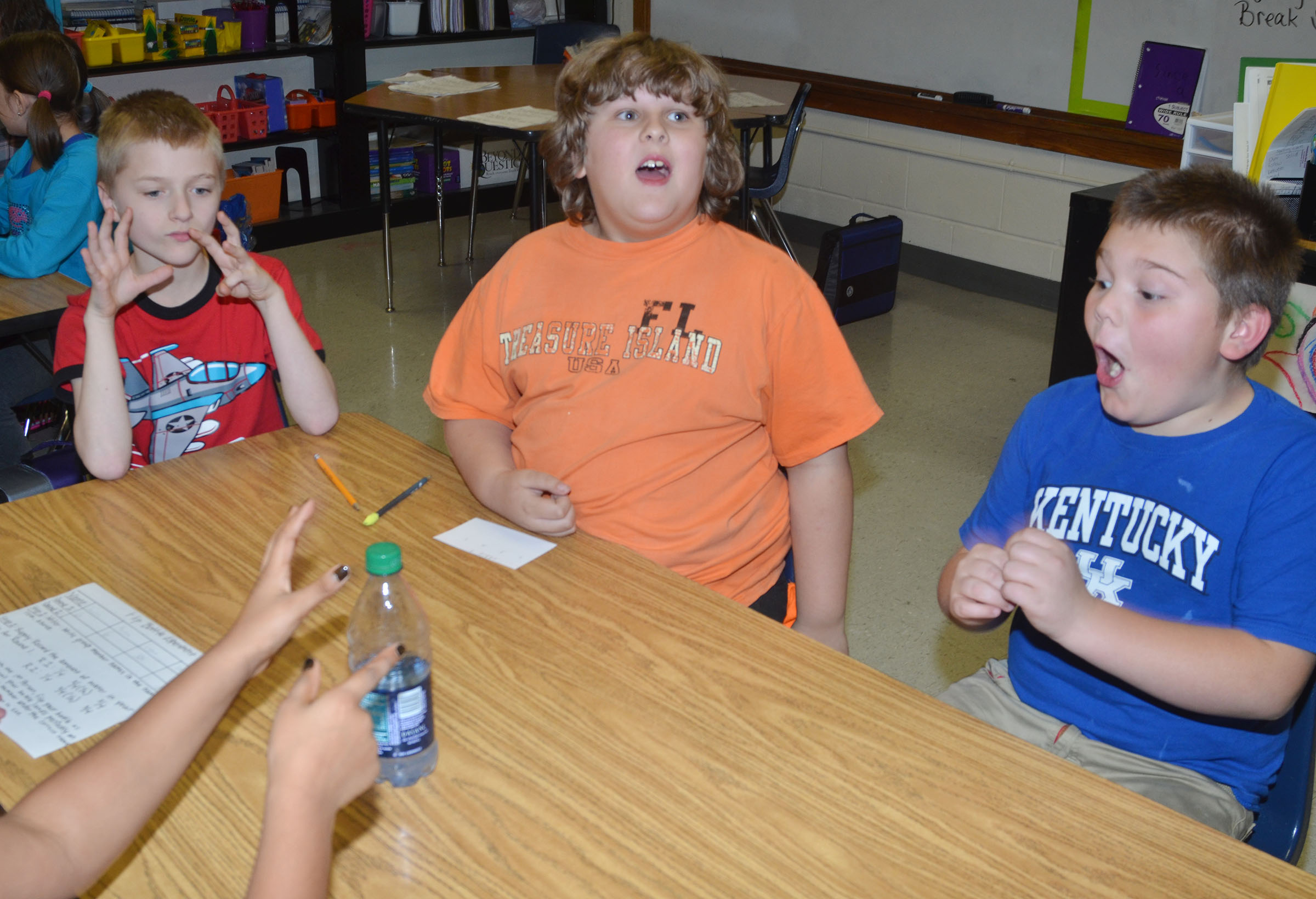 CMS fourth-grader Logan England reacts as his bottle lands correctly, along with classmate Zeke Harris, center. Tre Shipione, at left, keeps count of how many times England has flipped the bottle.