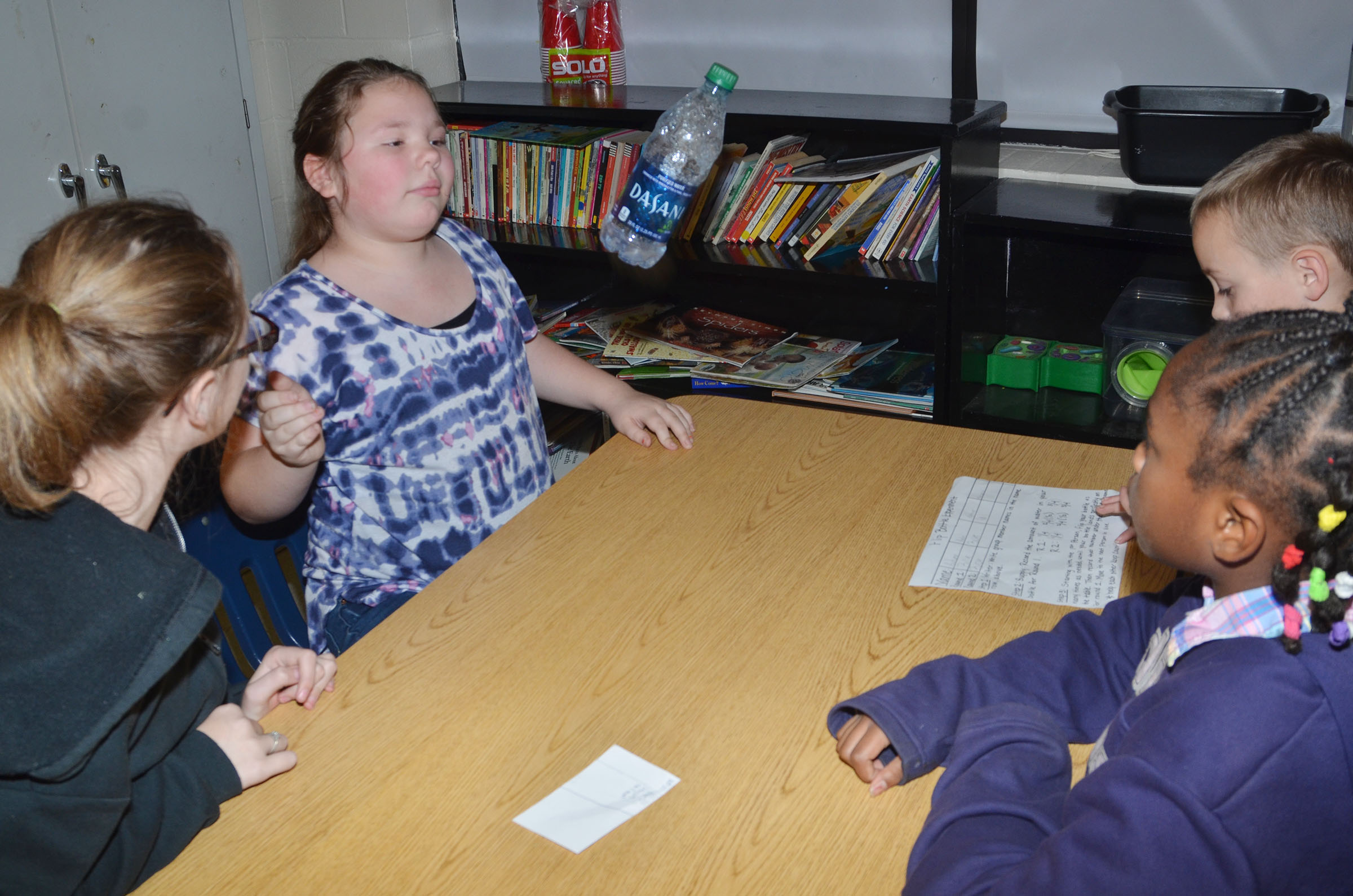 CMS fourth-grader Averi Perkins flips her water bottle as her groupmates watch.