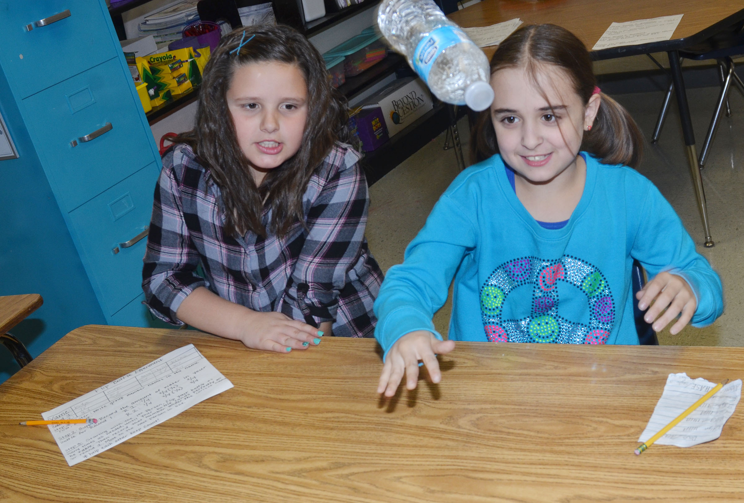 CMS fourth-grader Anna Floyd flips her water bottle, as classmate Kaitlyn Keith watches.