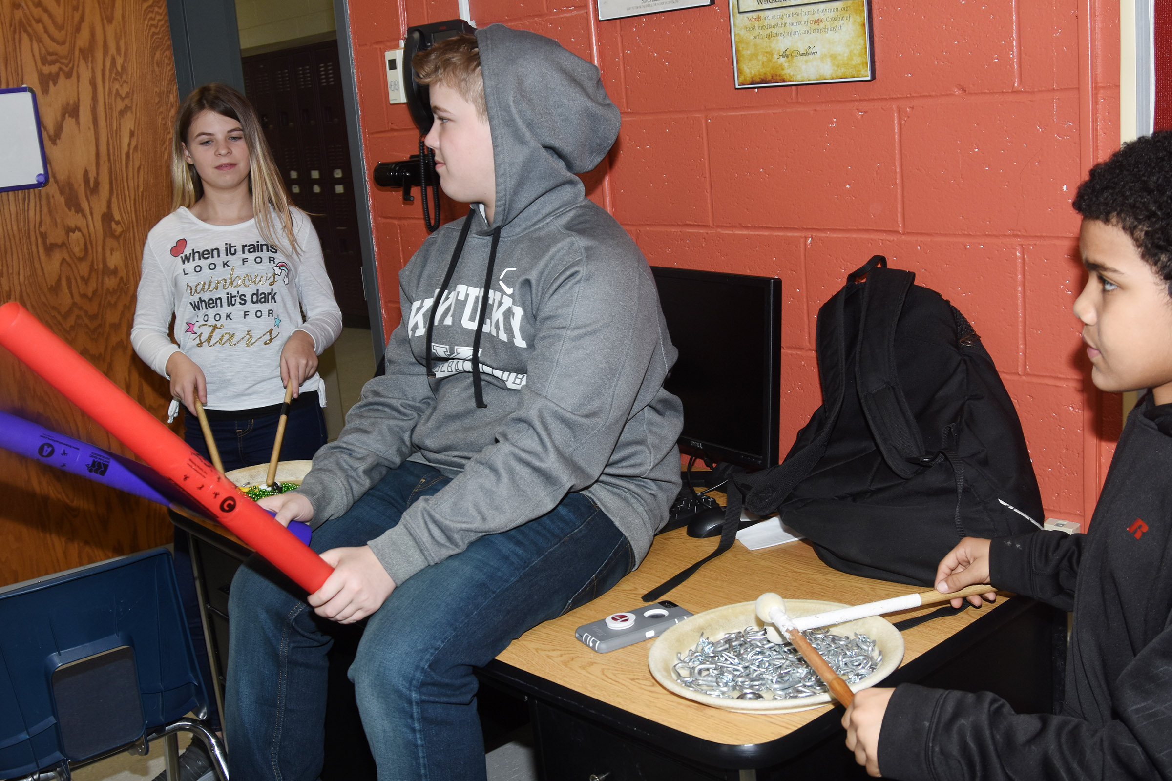 "From left, CMS sixth-graders Aryanna Britton, Ryan Grubbs and Tashaun Hart play ""Believer"" on their instruments."