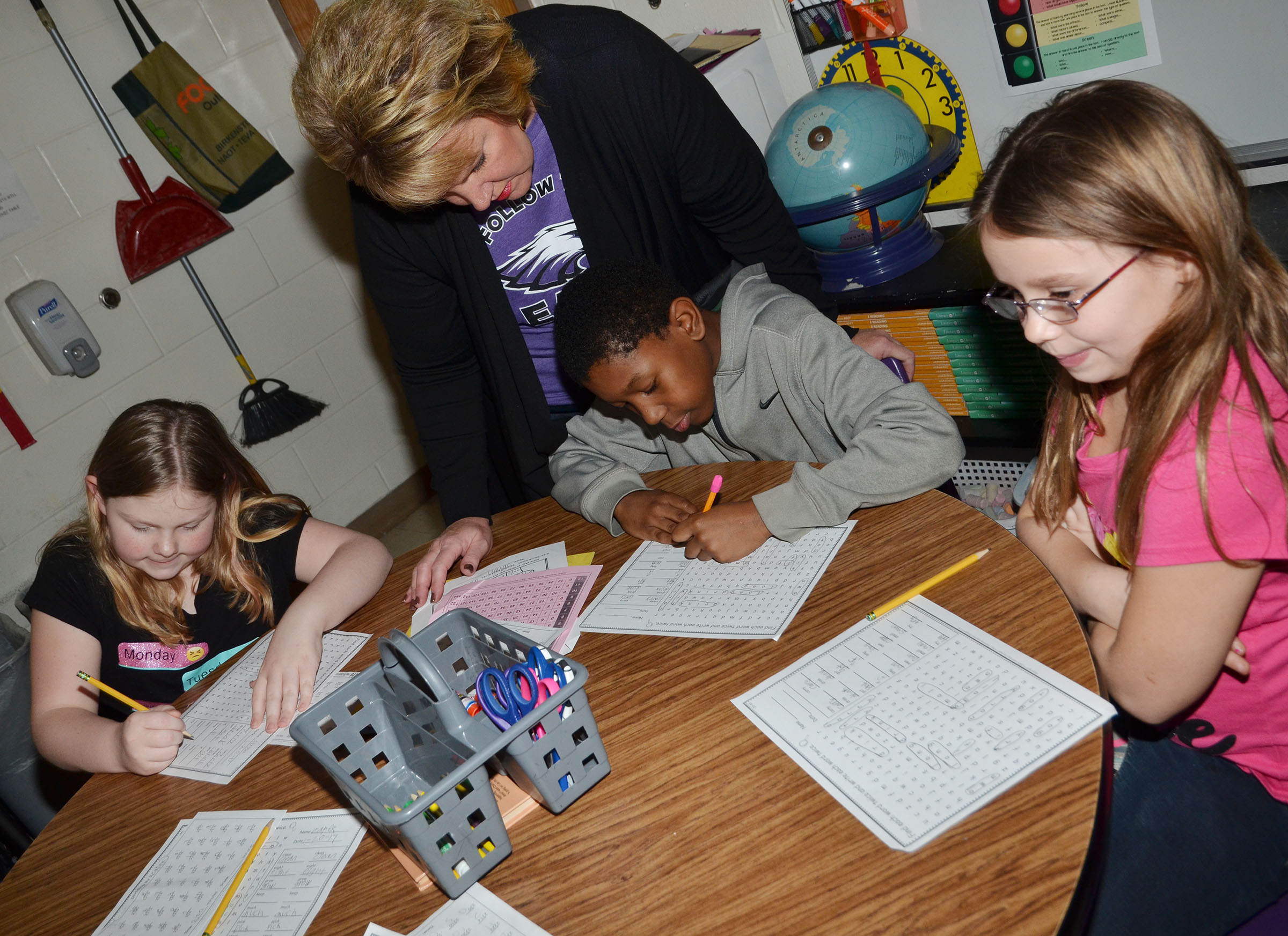 CMS fourth-grade teacher Kaye Agathen helps CES third-graders, from left, Alyssa Bennett, Jaron Johnson and McKailynn Grubaugh with a word search.