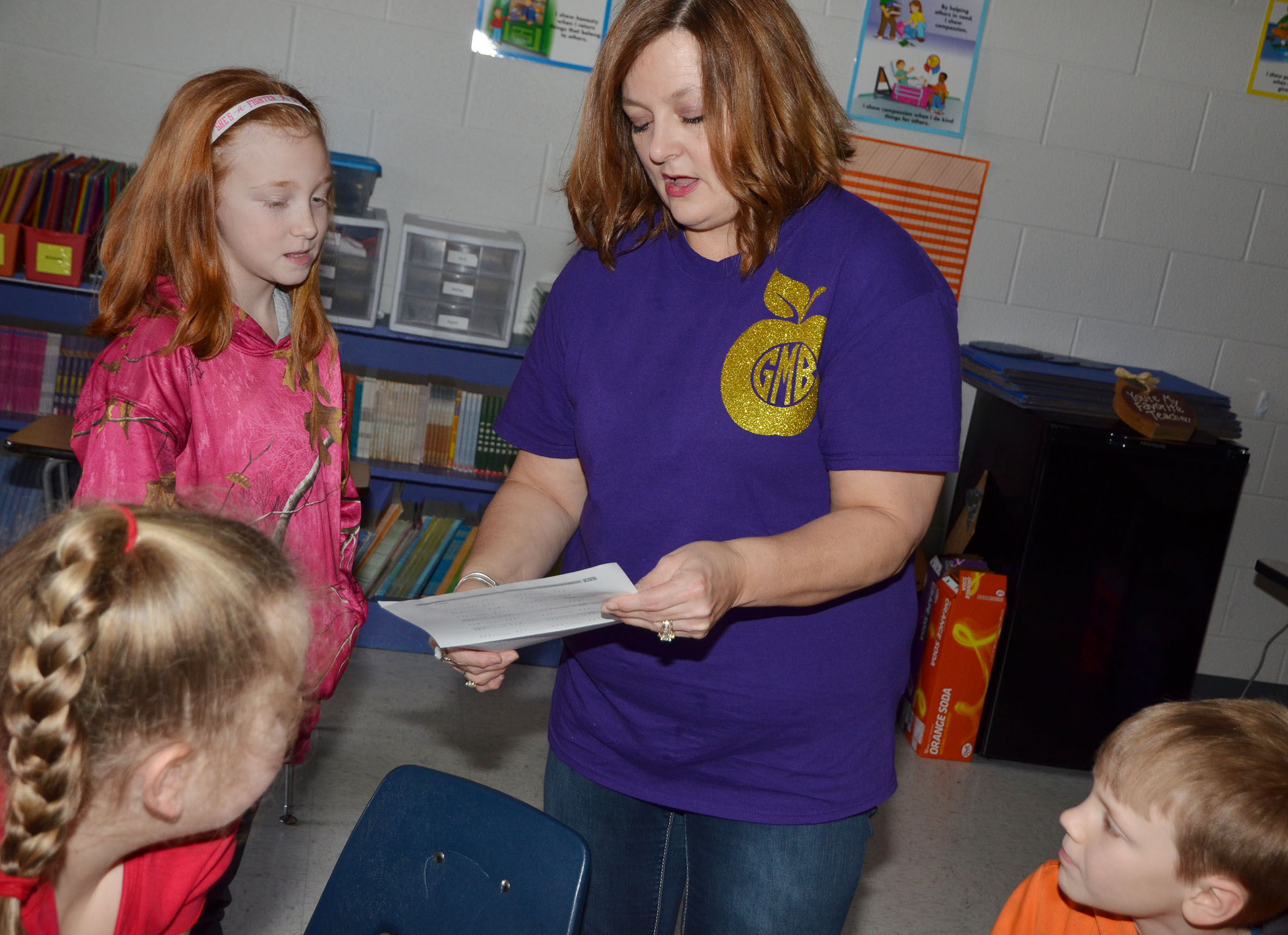CMS fourth-grade teacher Garnetta Murrell helps CES third-grader Savannah Wethington with a worksheet.