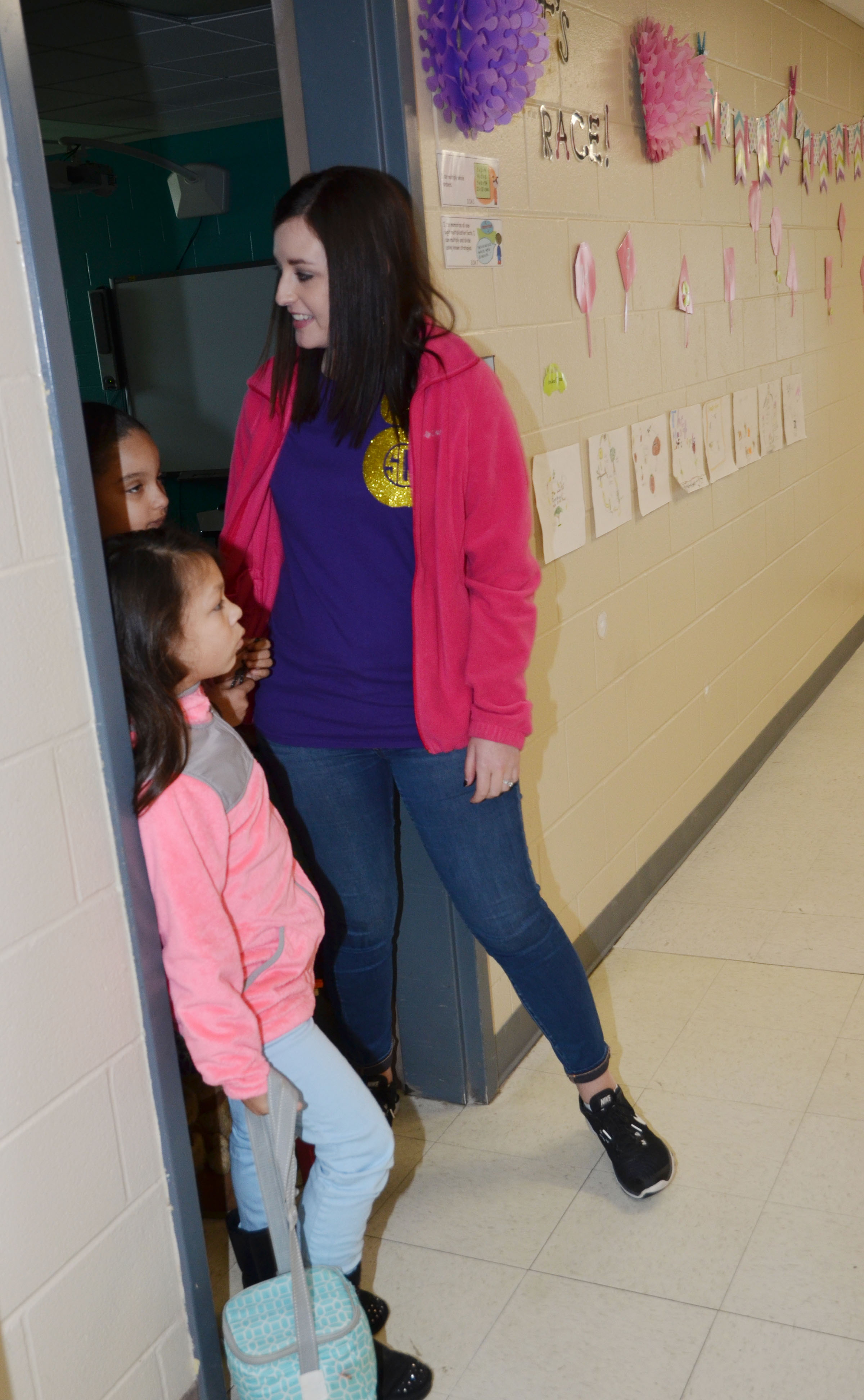 CMS fourth-grade teacher Samantha Coomer helps CES third-graders get ready to go home at the end of the day.