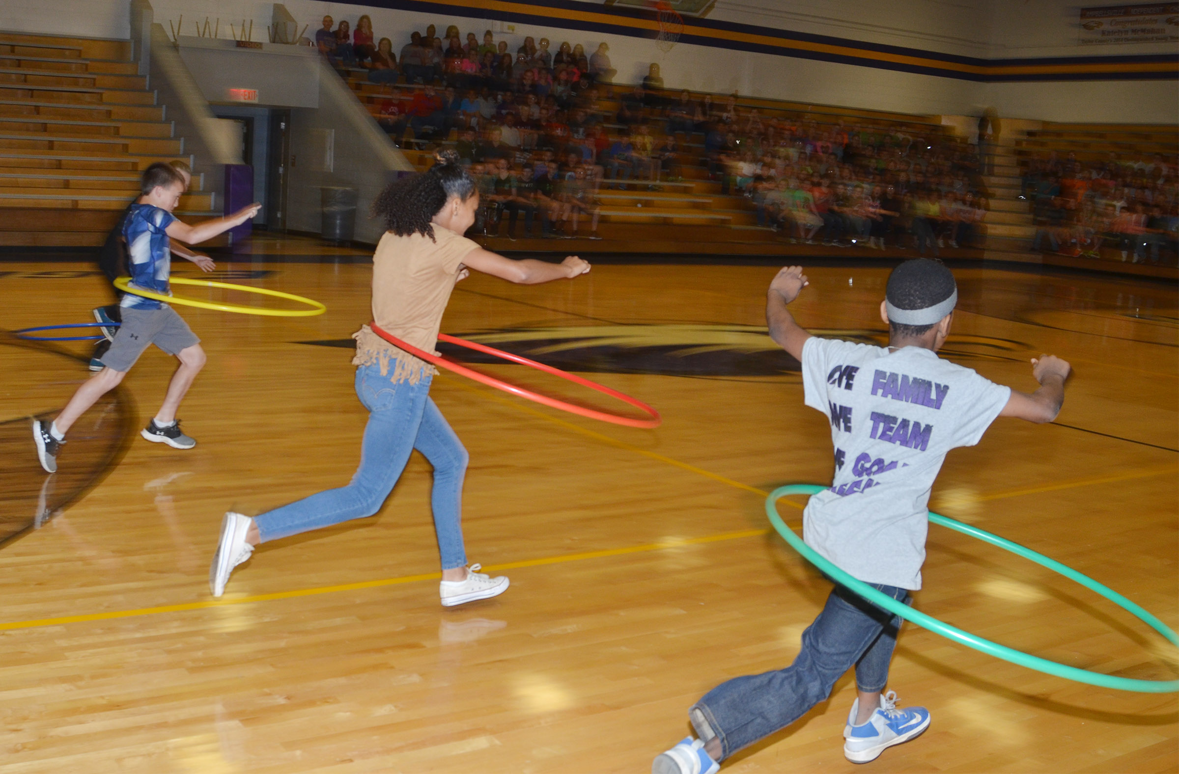From left, CMS sixth-grader Chase Hord and seventh-graders Alexis Thomas and Jadan Furman run with their hula hoops.