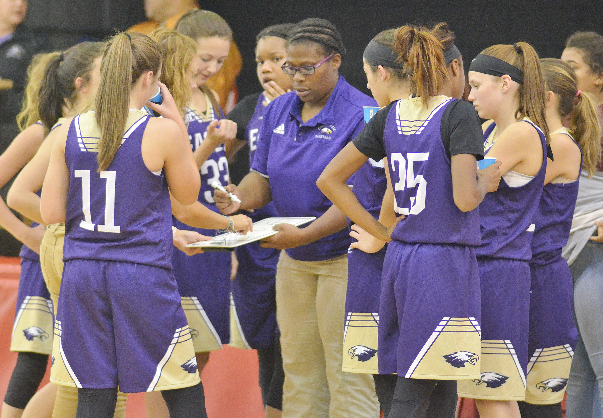 CMS head girls' basketball coach Tiarra Cecil talks with her players during a time out.