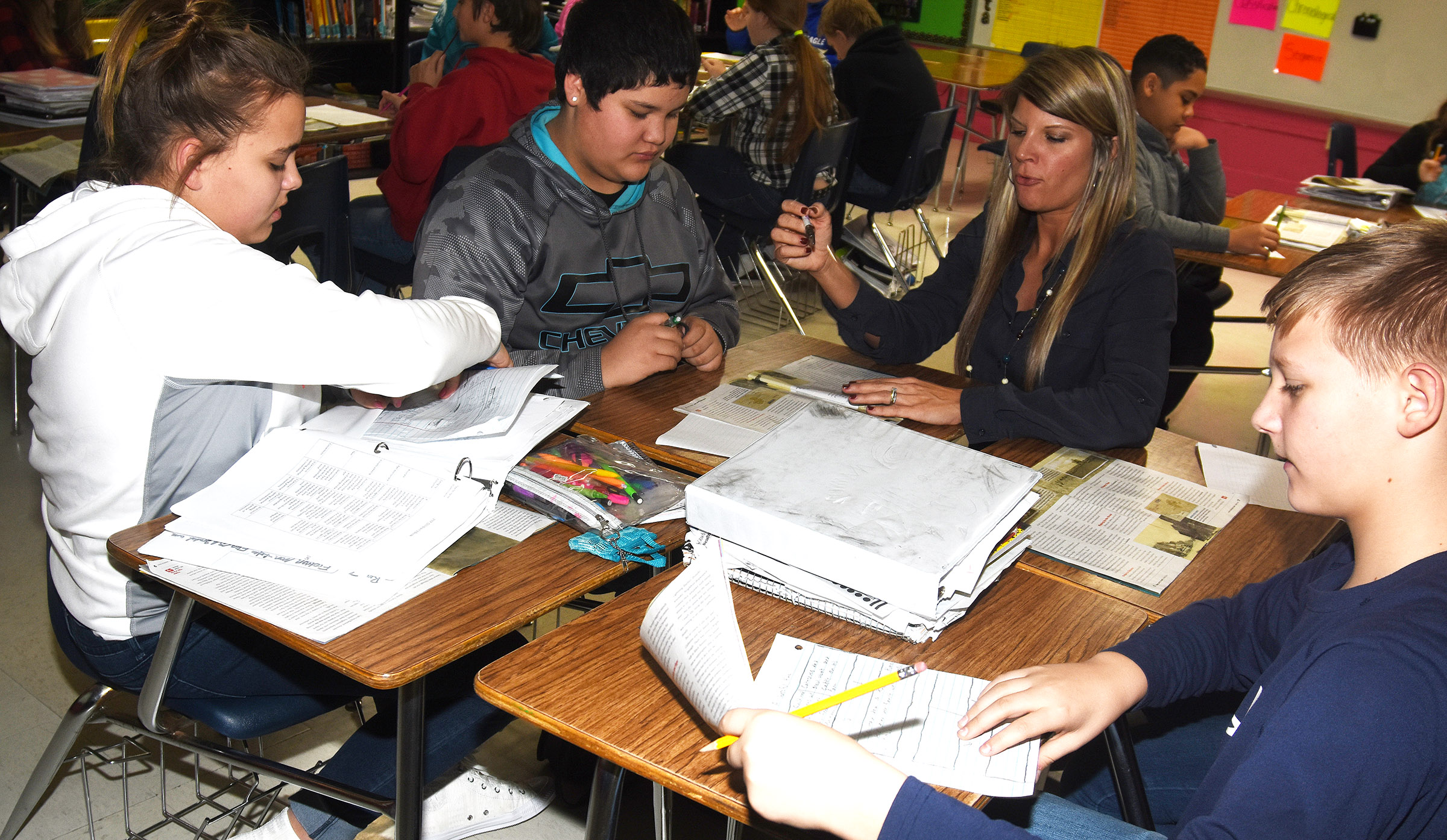CMS teacher Andrea Gribbins talks with, from left, sixth-graders Brooklyn Mays, Xavier Florez and Jesse King about identifying the main idea in a story.