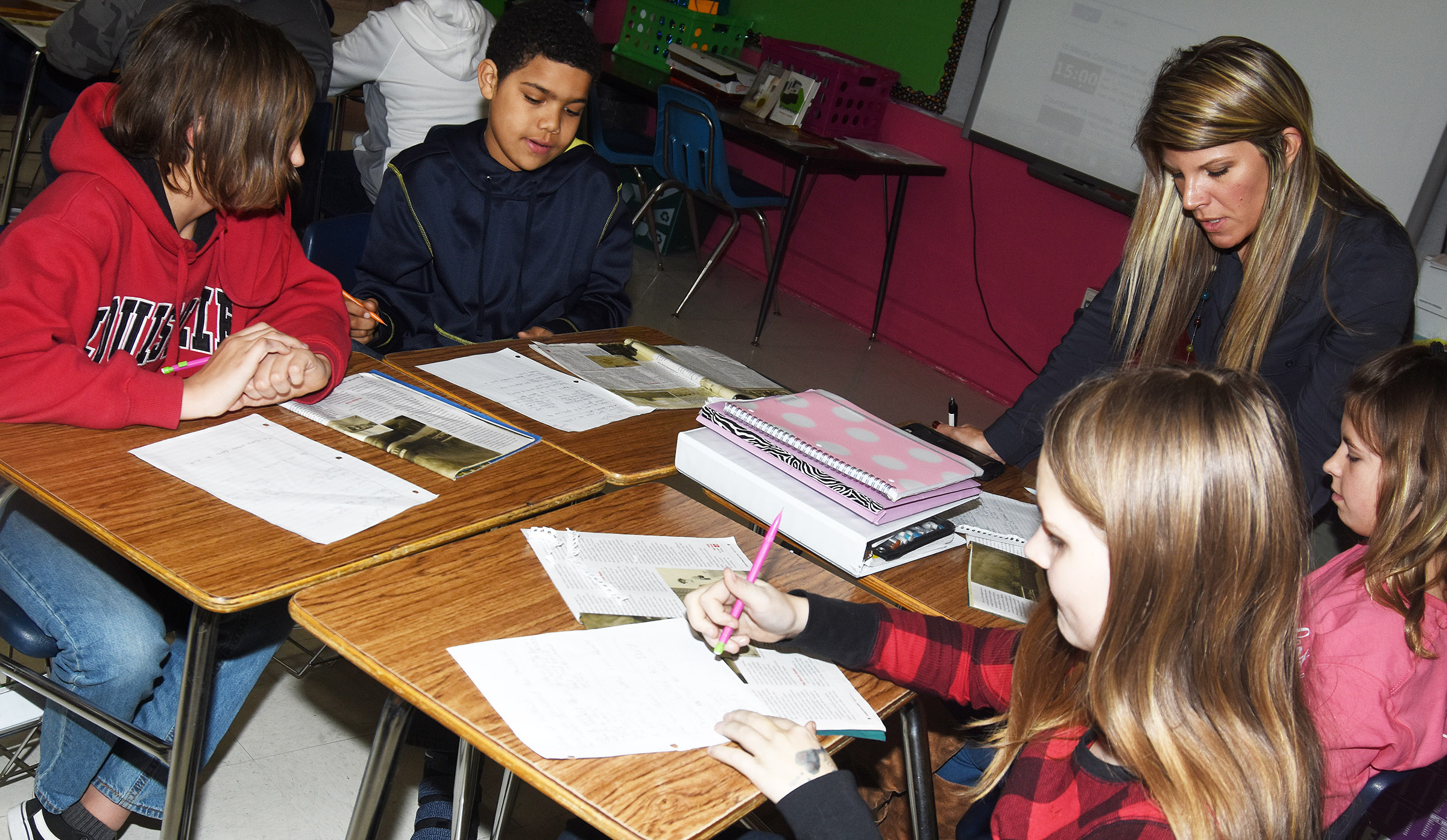 CMS teacher Andrea Gribbins talks with, from left, sixth-graders Ethan Taylor, Tashaun Hart, Mallory Parker and Aryanna Britton about how to find details in a story that support the main idea.