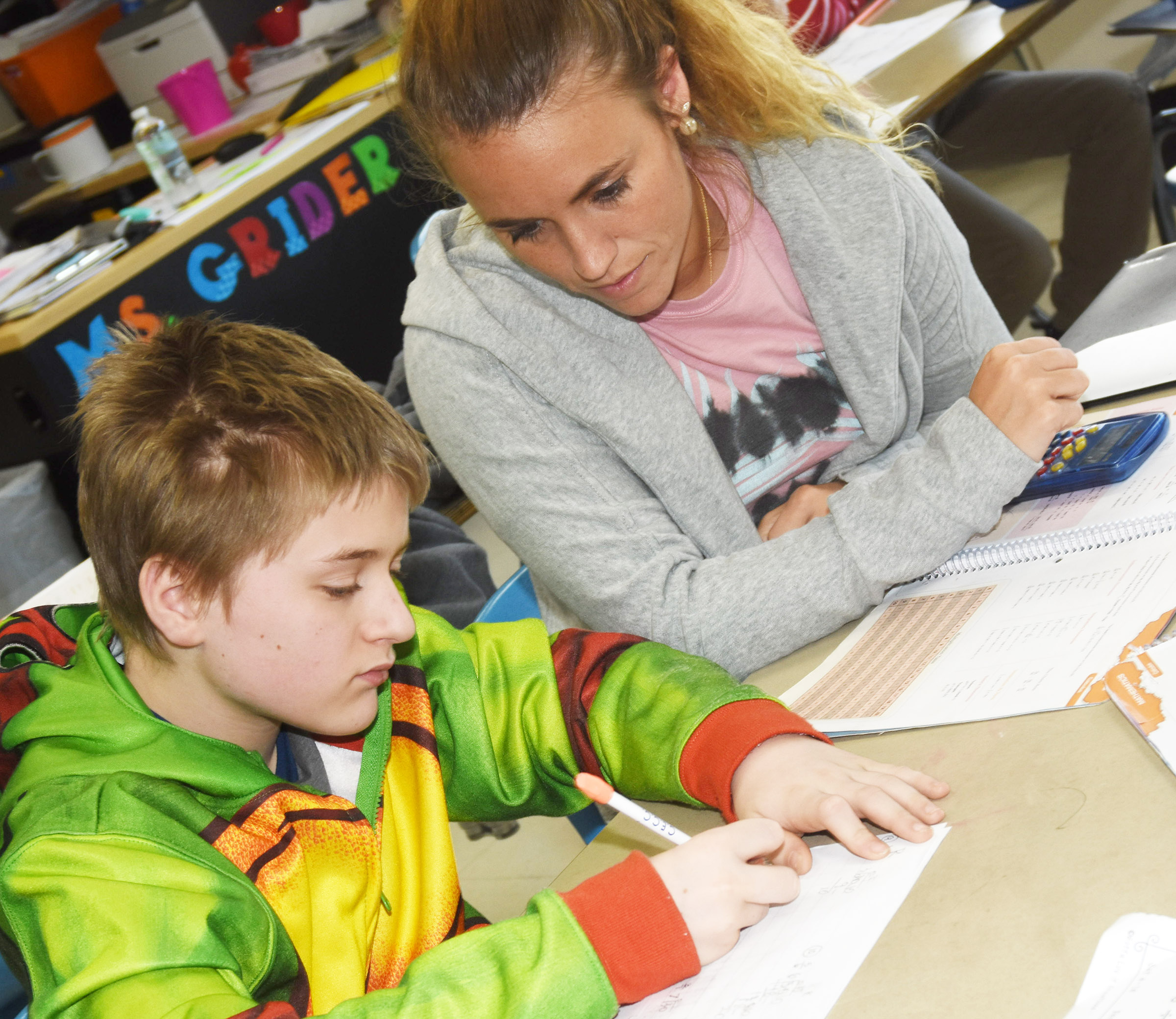 CMS teacher LeeAnn Grider works with sixth-grader Tre Shipione as he practices converting fractions to decimals.