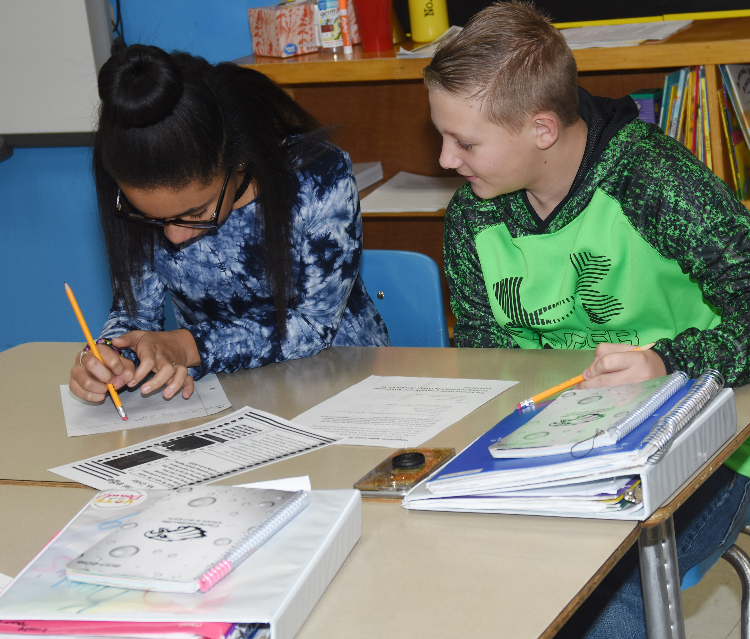 "CMS sixth-graders Keely Thompson, at left, and Jesse King work together to create a ""survival guide"" for new CMS teacher LeeAnn Grider."