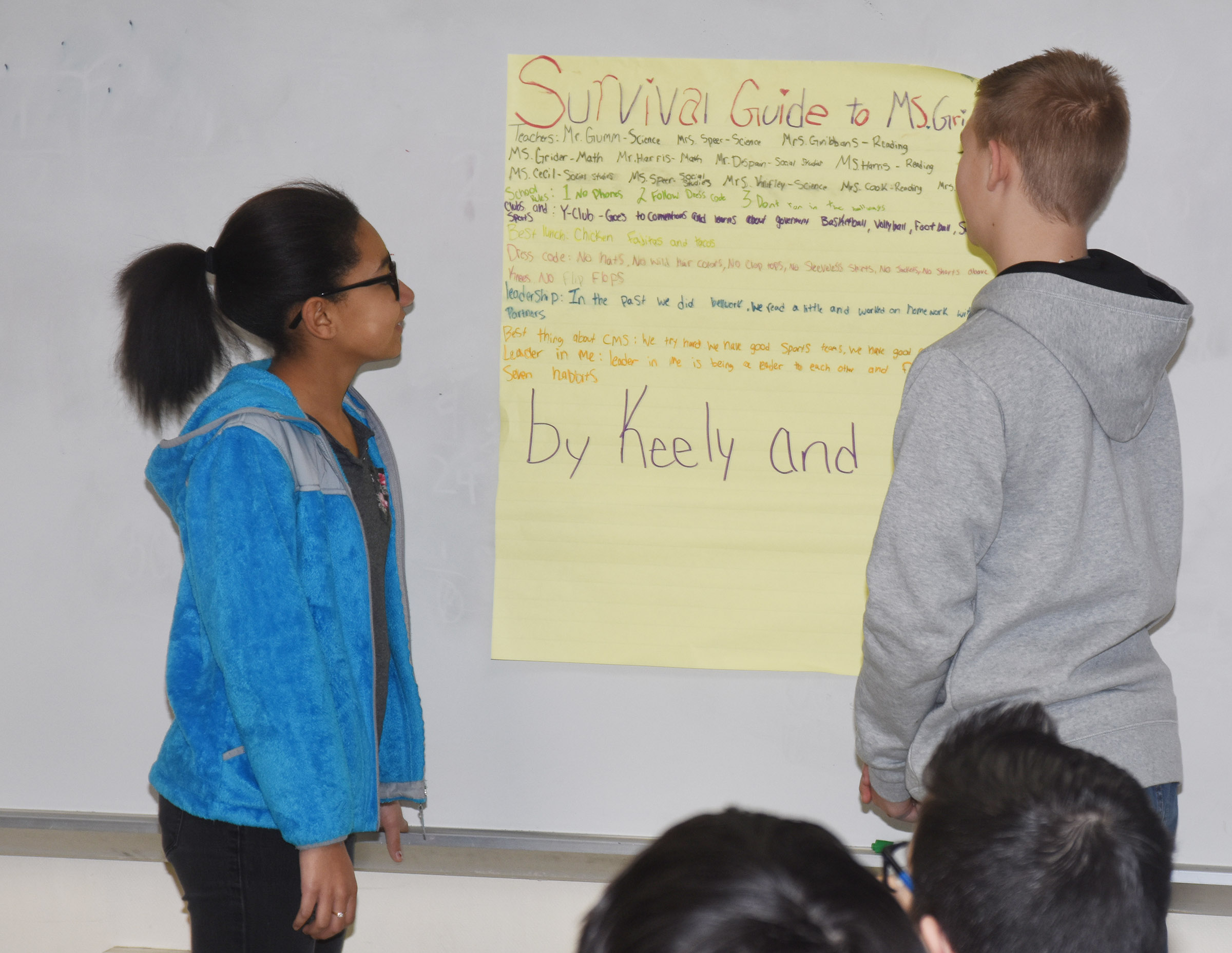 "CMS sixth-graders Keely Thompson, at left, and Jesse King present their ""survival guide"" to help teacher LeeAnn Grider learn about her new school."