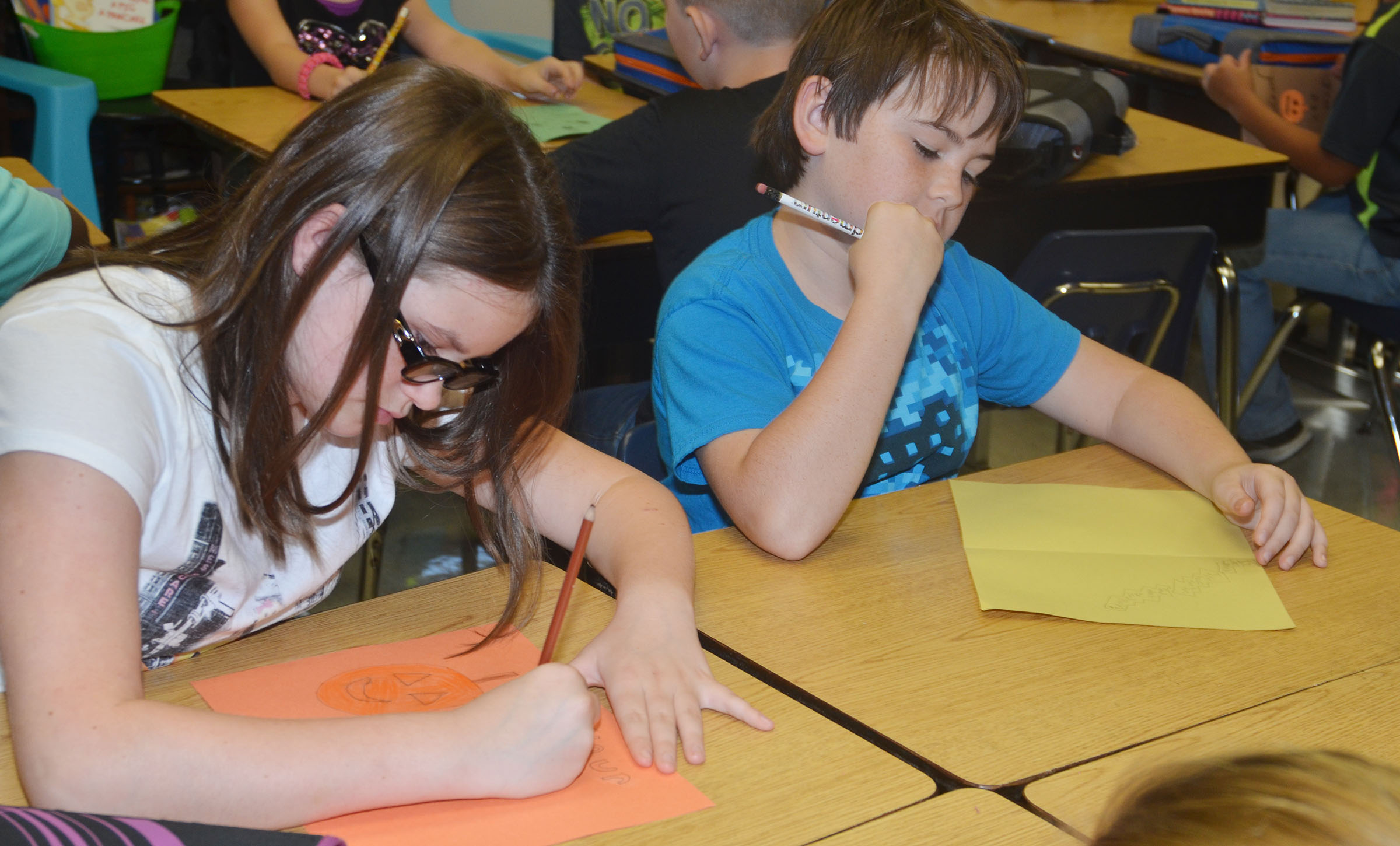 CMS fourth-graders Lydia Miller, at left, and Cody Agee work on their cards.