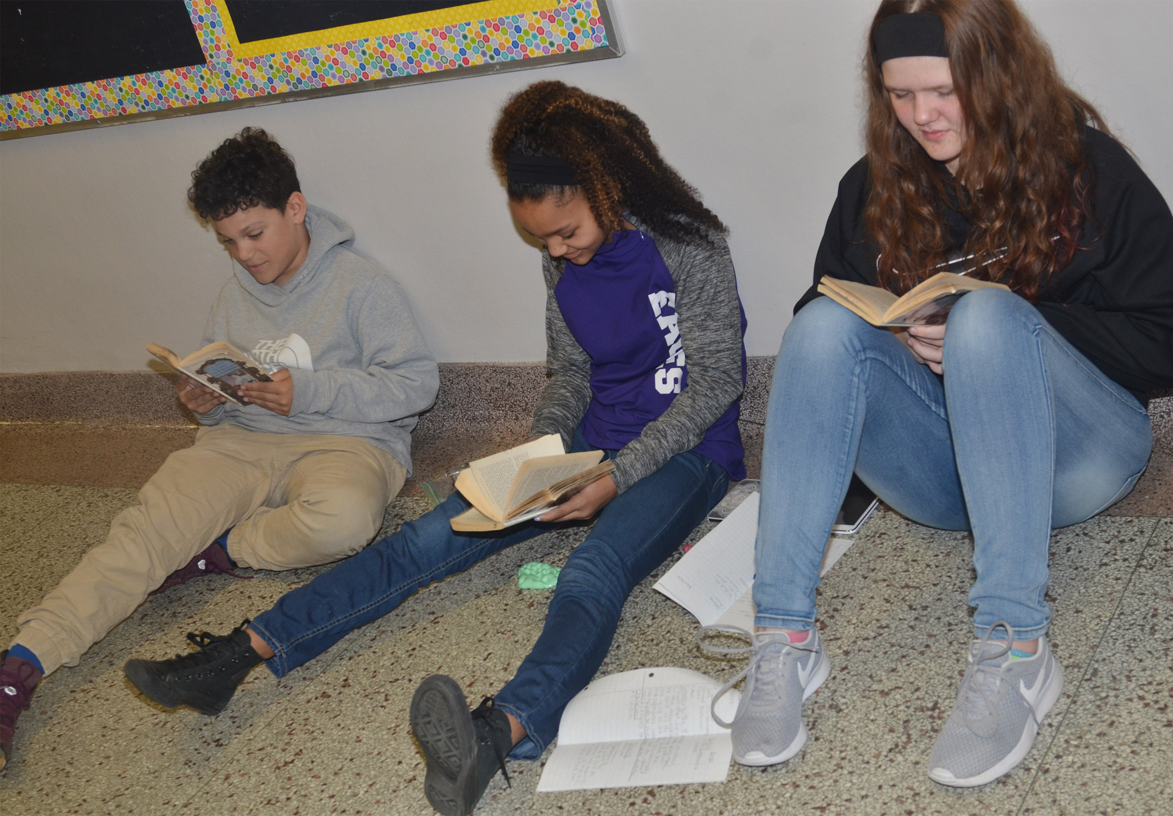 From left, CMS sixth-grader Kaydon Taylor and seventh-graders Alexis Thomas and Autumn Brown read together.
