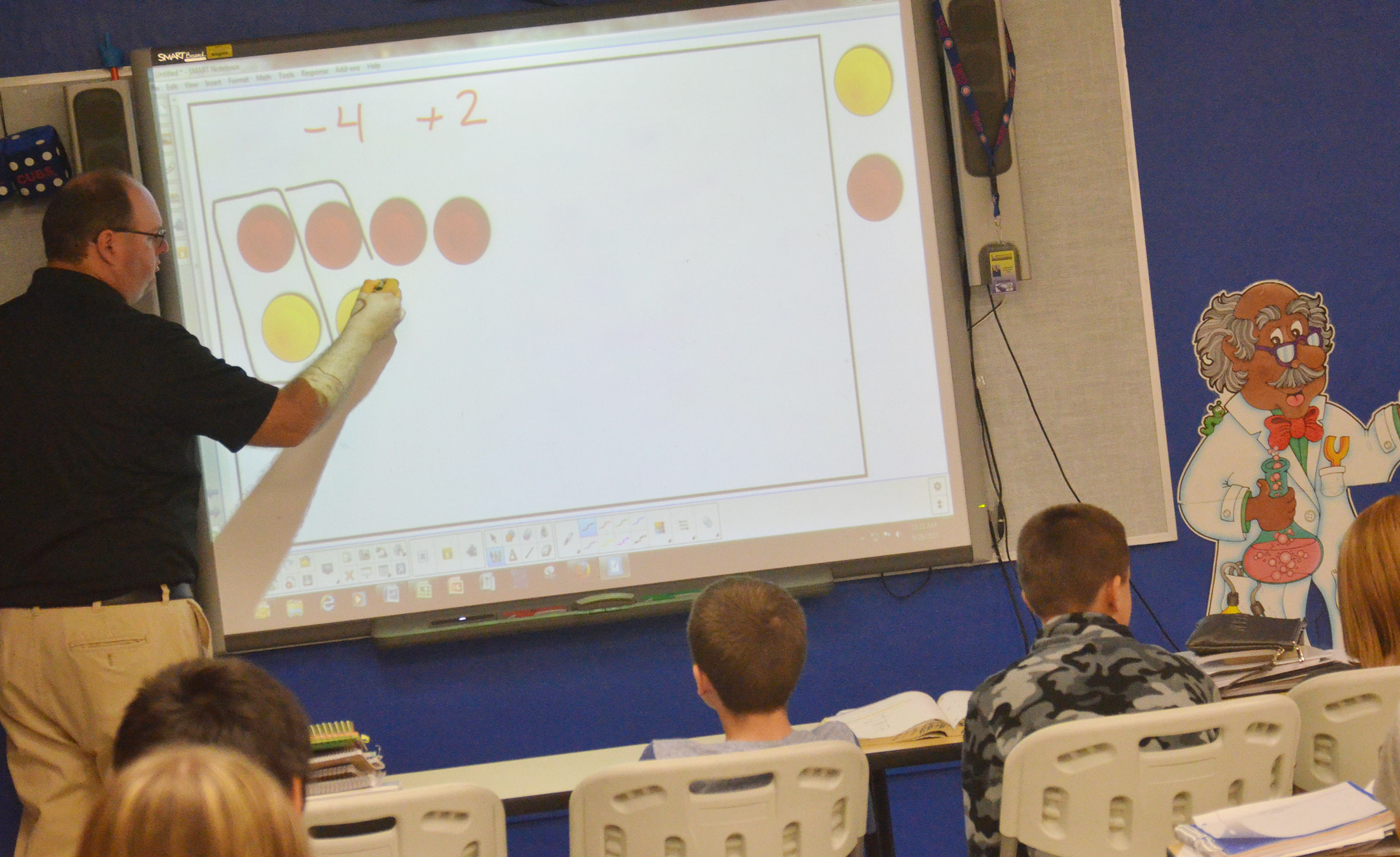 CMS teacher Steven Gumm shows students how to work a math problem using their counters.