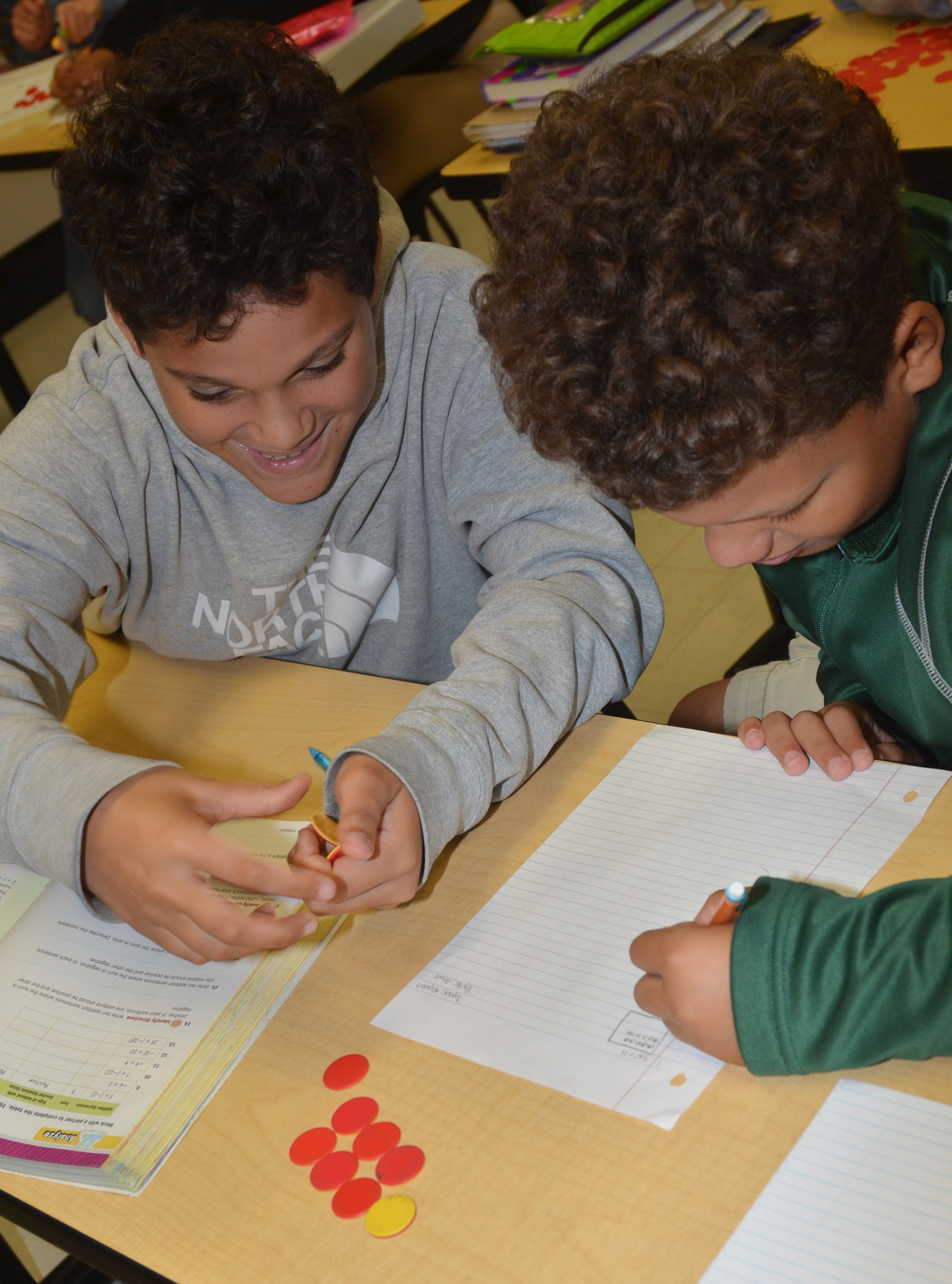 CMS seventh-graders Kaydon Taylor, at left, and Amare Poynter work a math problem with their counters.