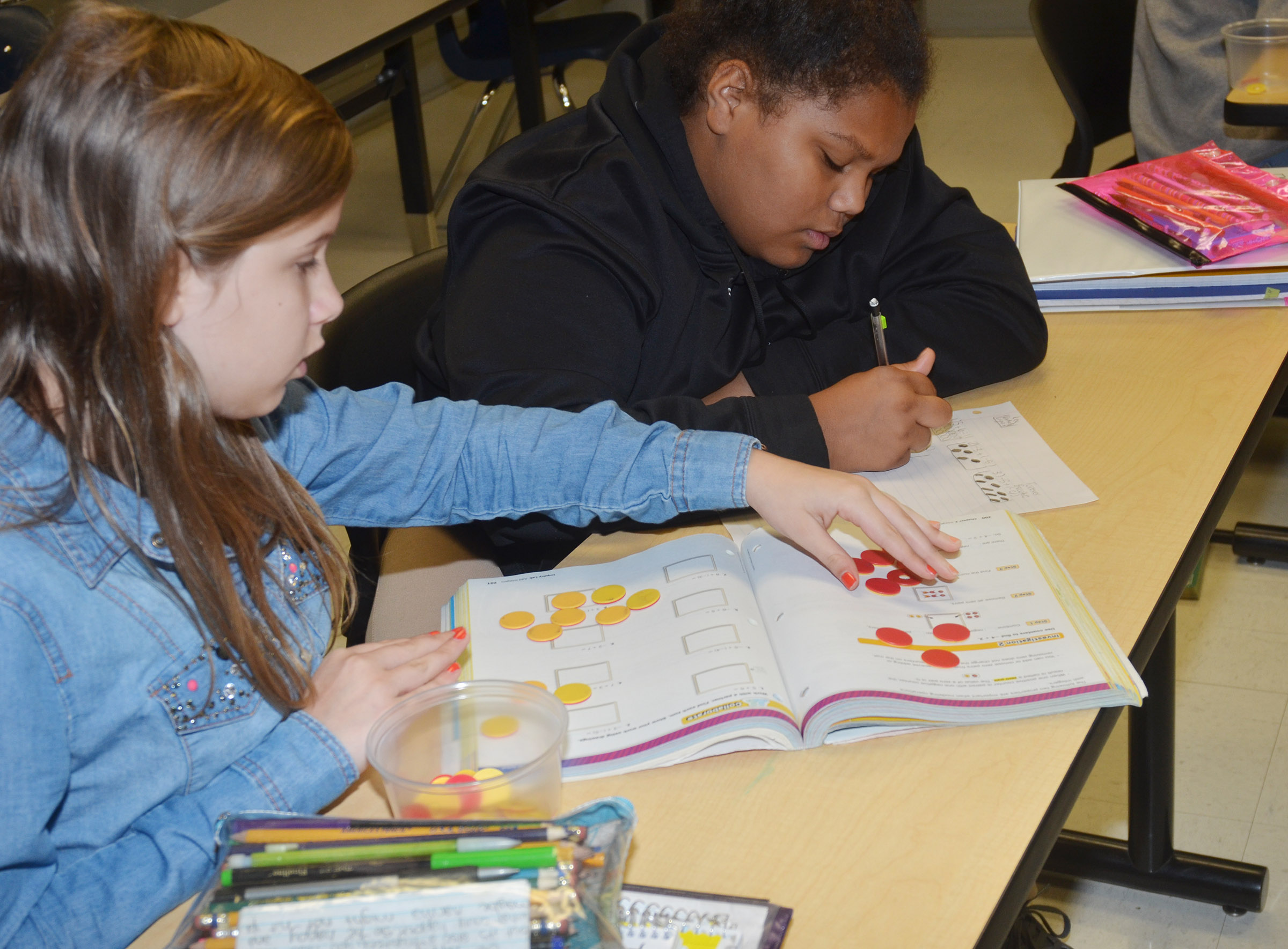 CMS seventh-graders Forever Tungate, at left, and Brooklyn Taylor work a math problem with their counters.