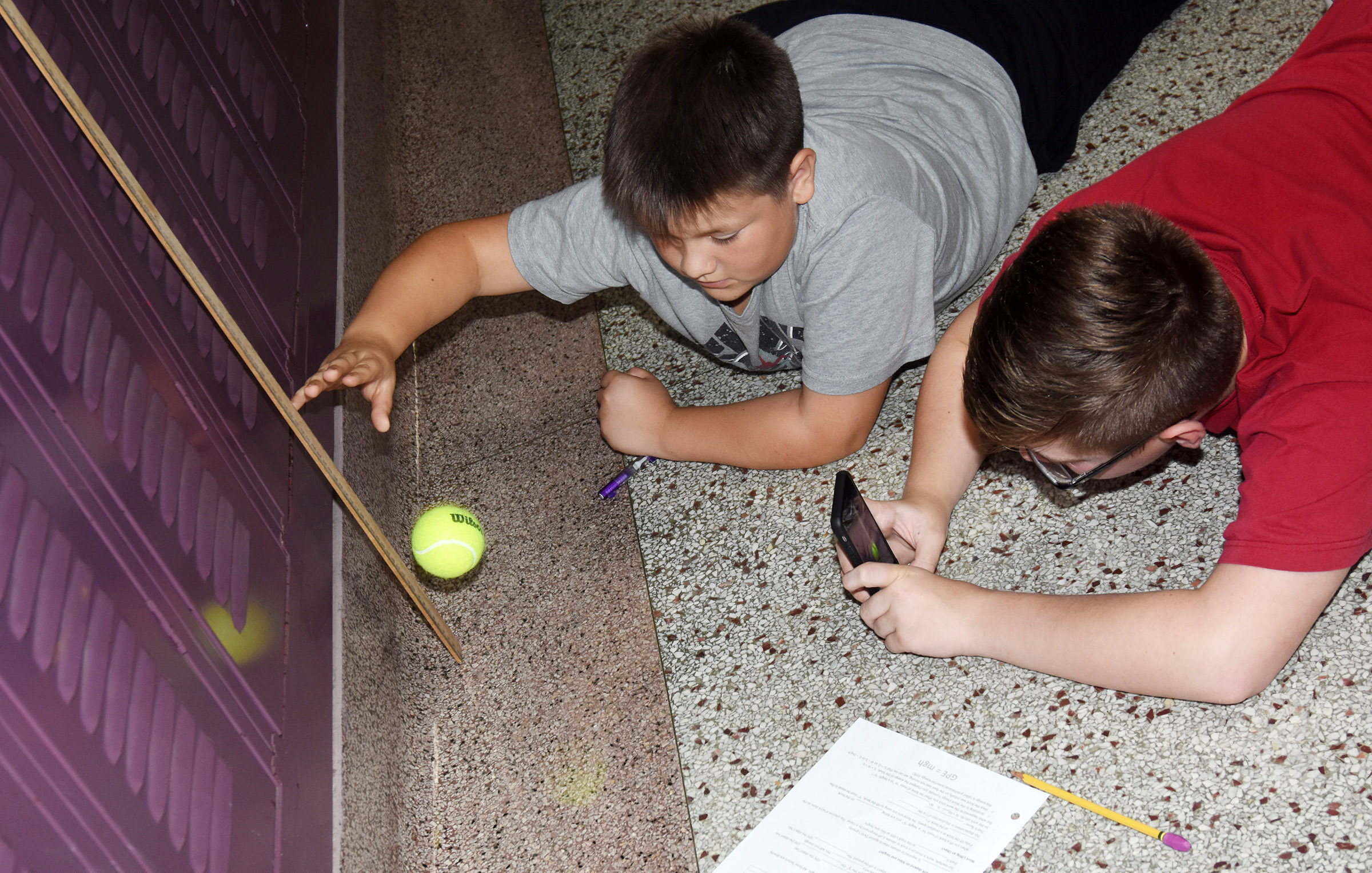 CMS seventh-graders Leo Lamer, at left, and Jovi Bowen record their data as they research the relationship between mass, gravitational acceleration and height.