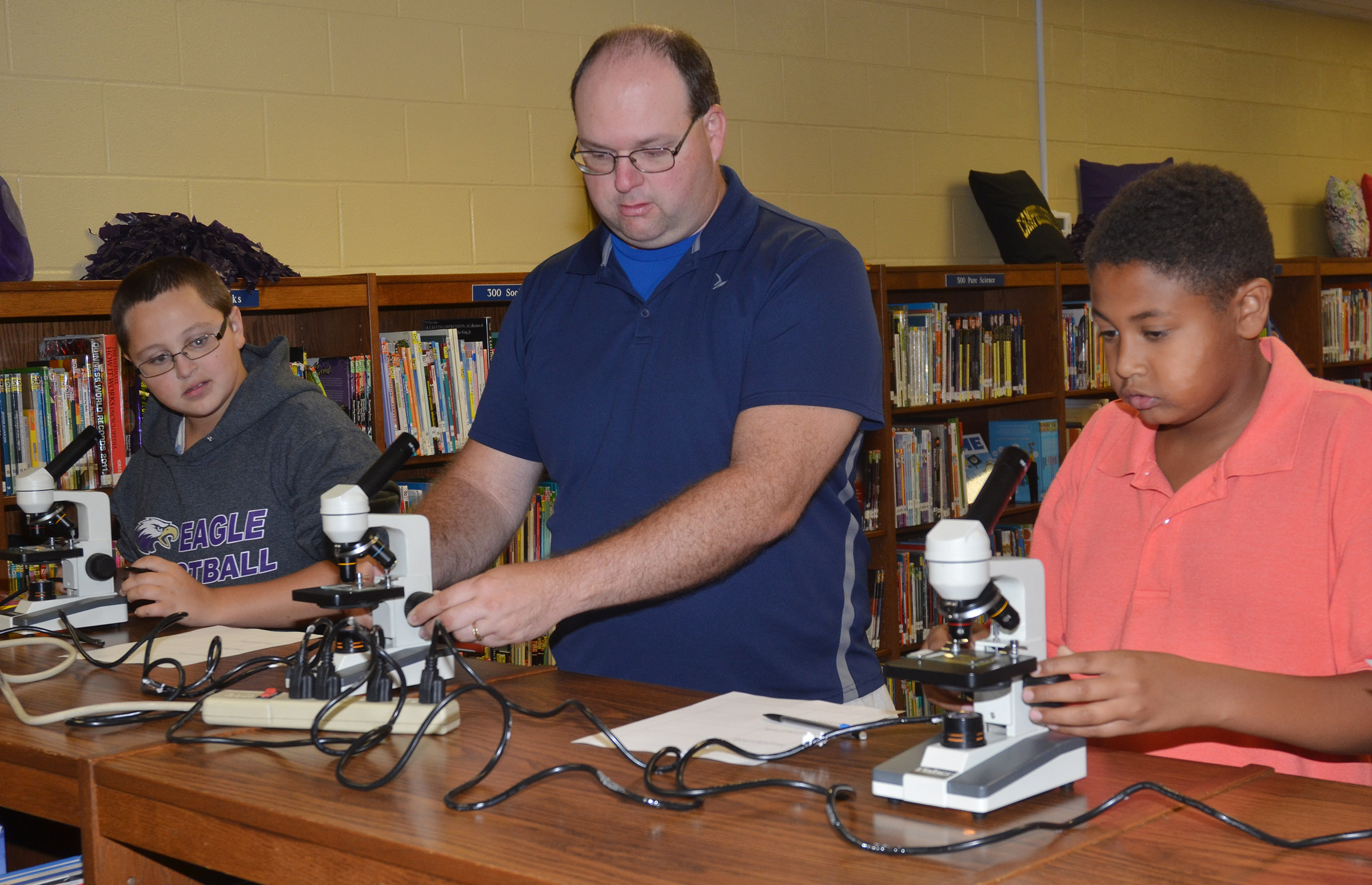 CMS teacher Steven Gumm talks to seventh-graders Cameron Mahan, at left, and Ronin Smith about how to use a microscope.