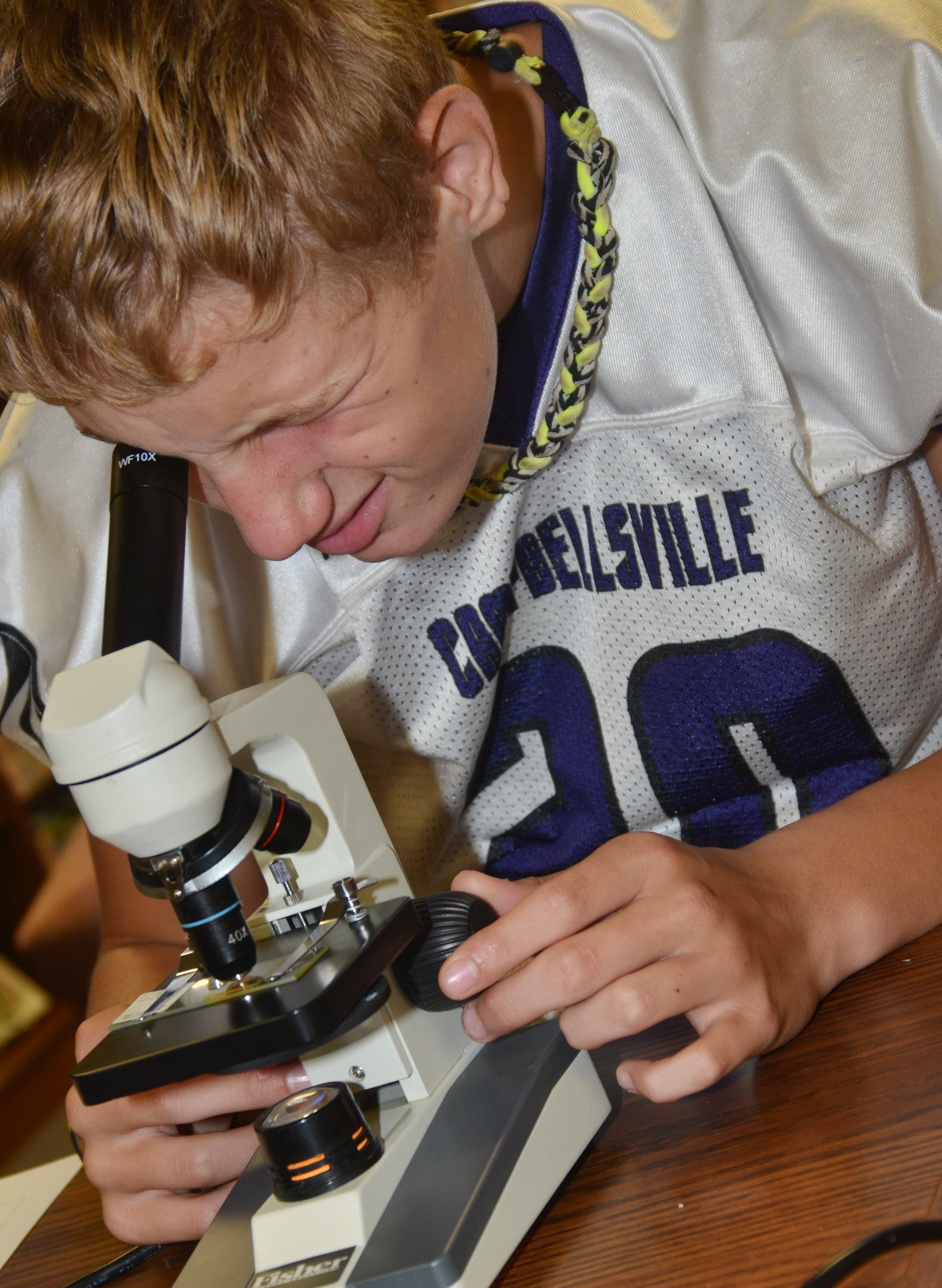 CMS seventh-grader Damon Johnson looks at a piece of thread under a microscope.