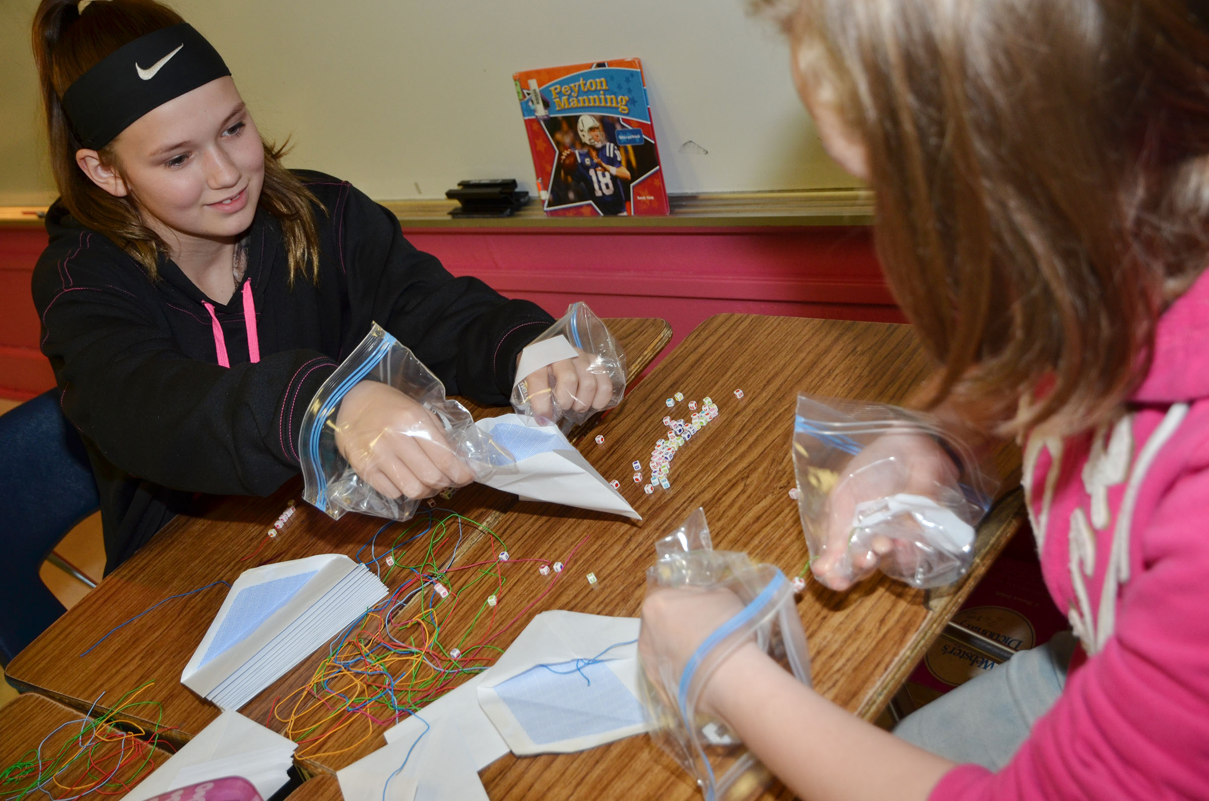 CMS sixth-grader BreAnna Humphress works with her groupmates to make bracelets while wearing zip lock bags for gloves.