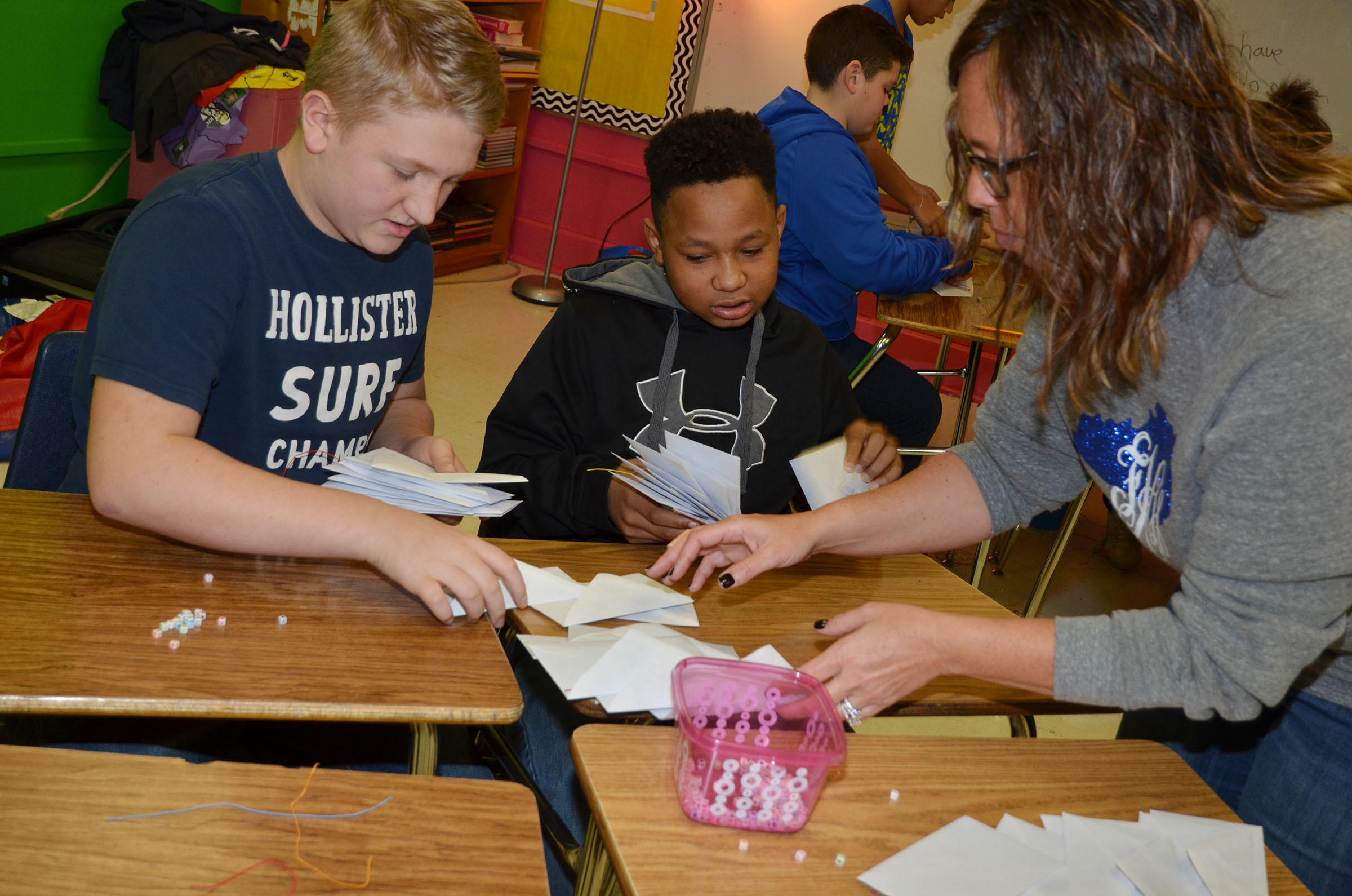 CMS sixth-grader teacher Farrah Hord helps students Levi Dicken, at left, and Deondre Weathers collect their packaged bracelets.