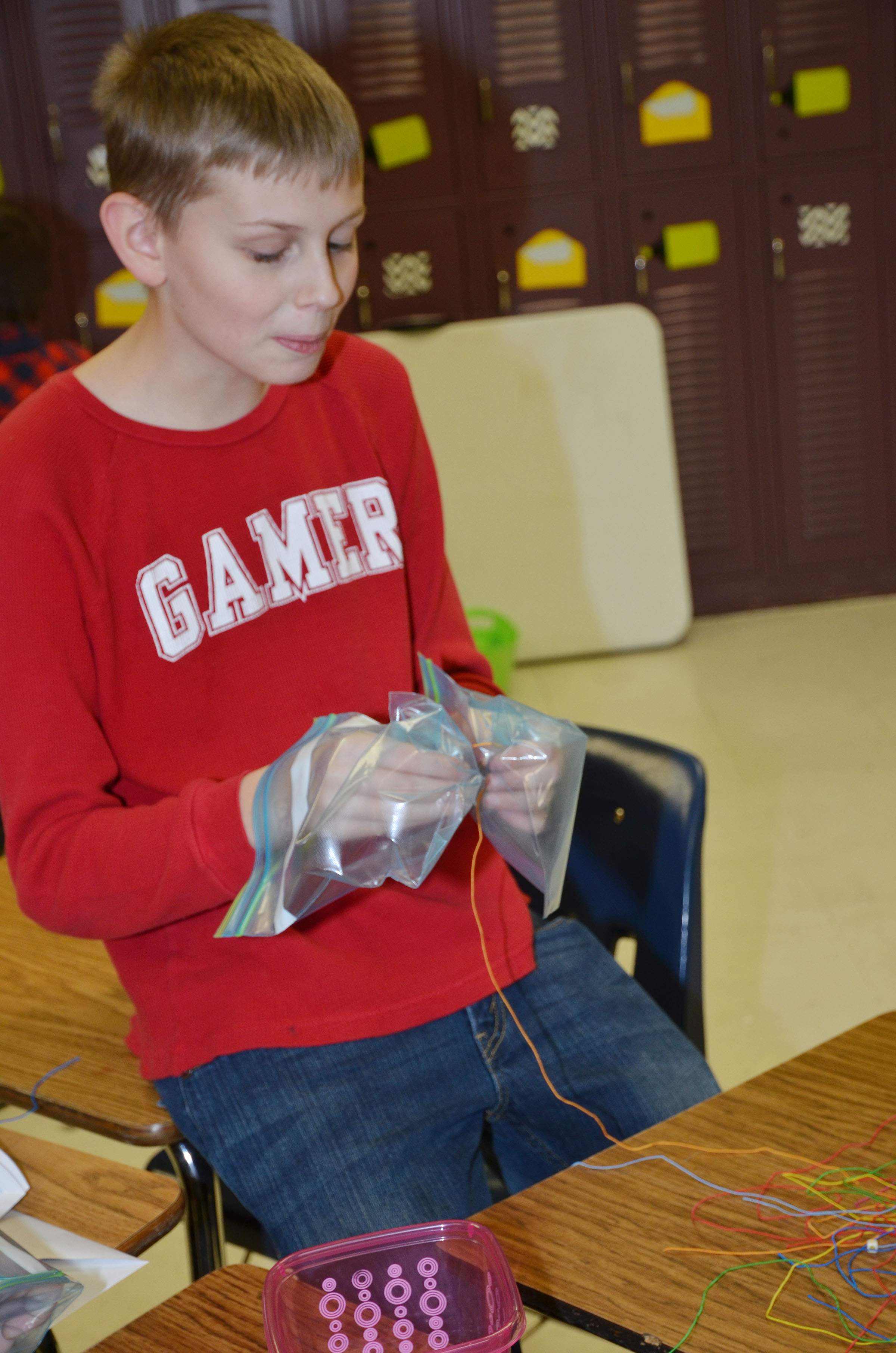 CMS sixth-grader Ethan Bright makes bracelets while wearing zip lock bags for gloves.