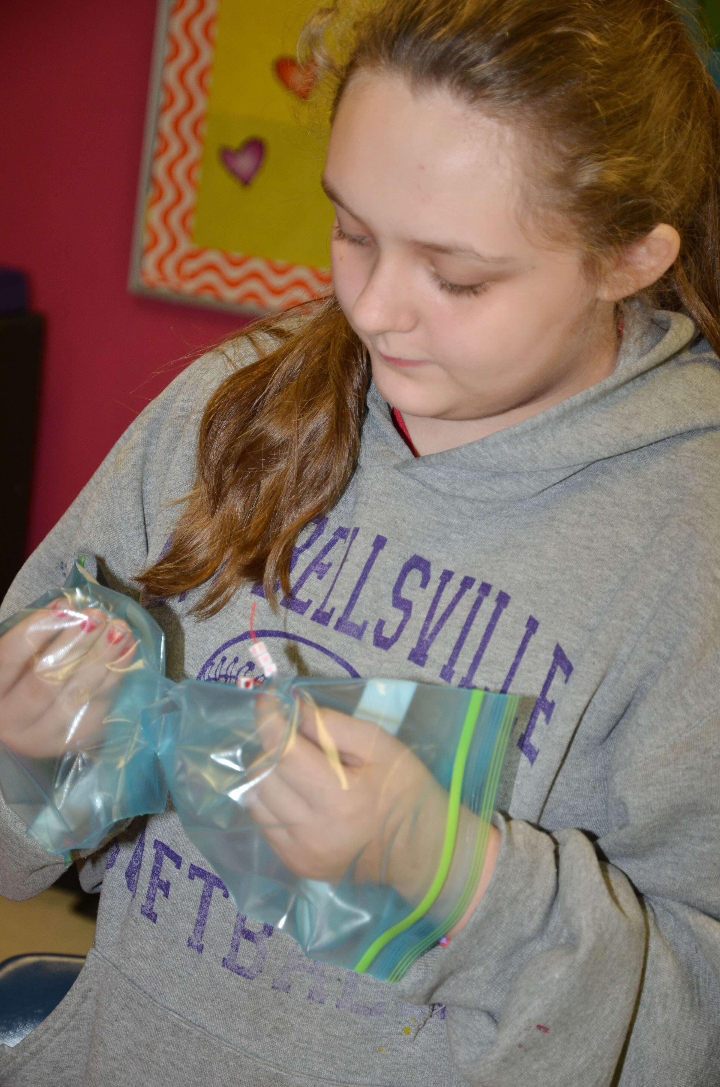 CMS sixth-grader Elizabeth Lopez makes a bracelet while wearing zip lock bags for gloves.