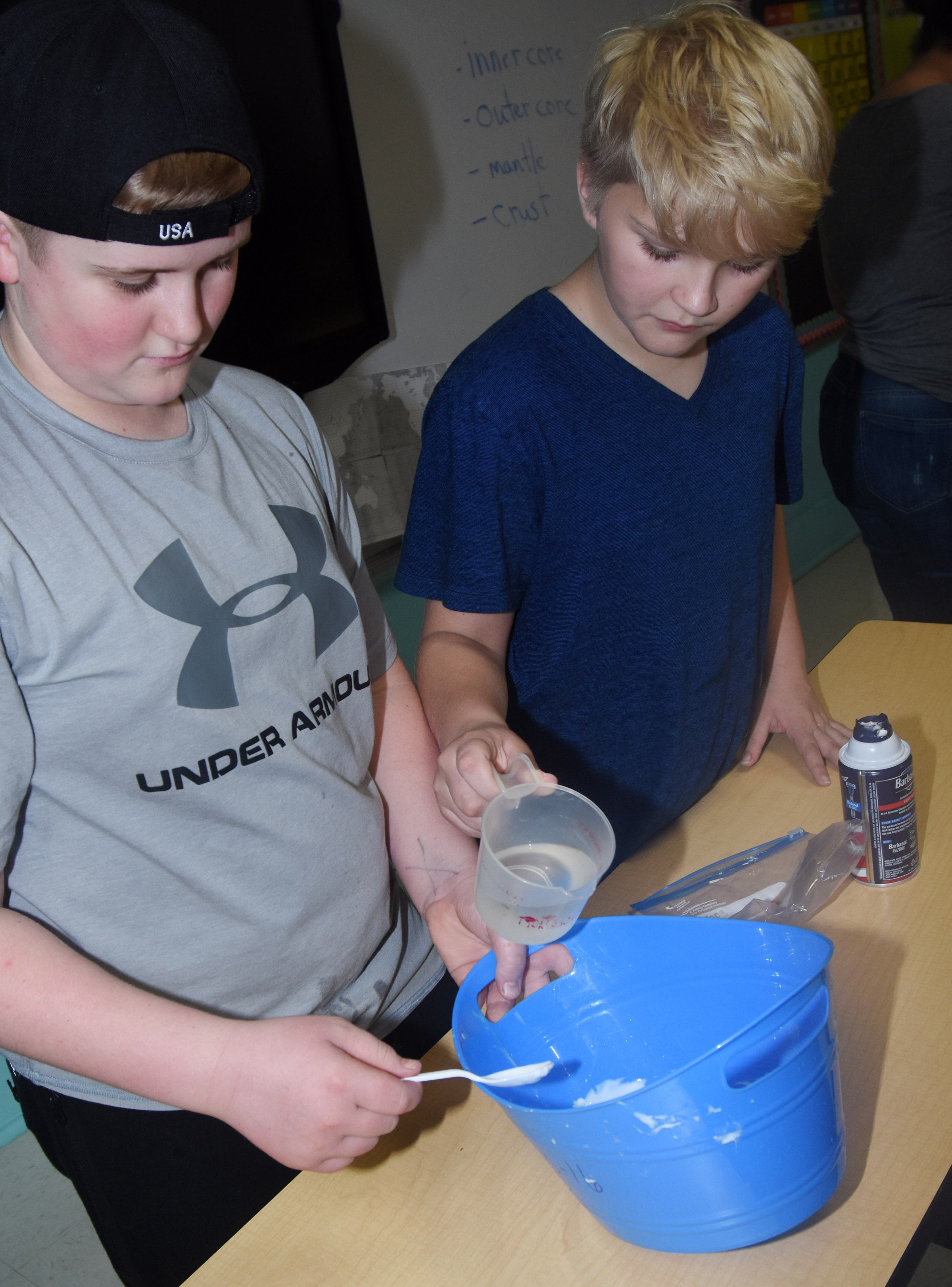 CMS sixth-graders Lance Knifley, at left, and Dakota Tungate mix together the ingredients to make slime.