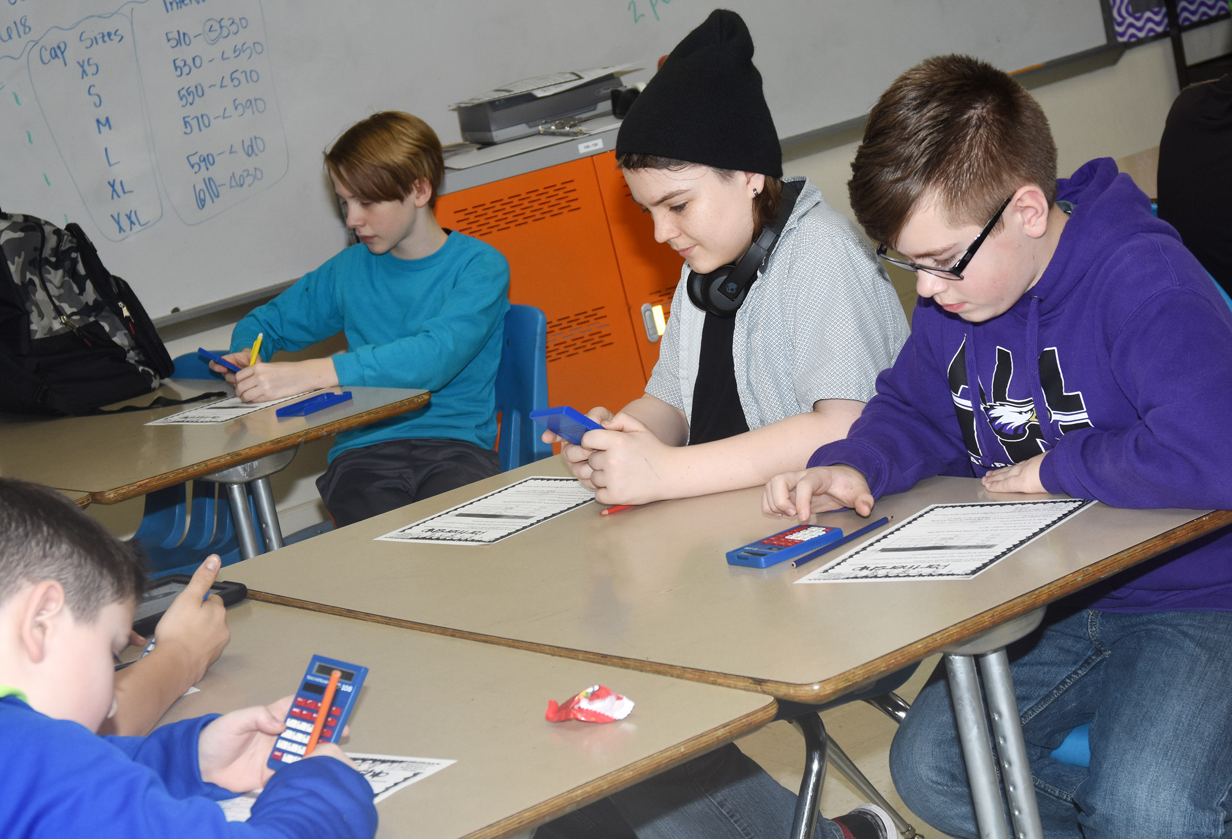 CMS sixth-graders, from left, Thomas Lucas, Kayden Birdwell and Jovi Bowen complete a math problem.