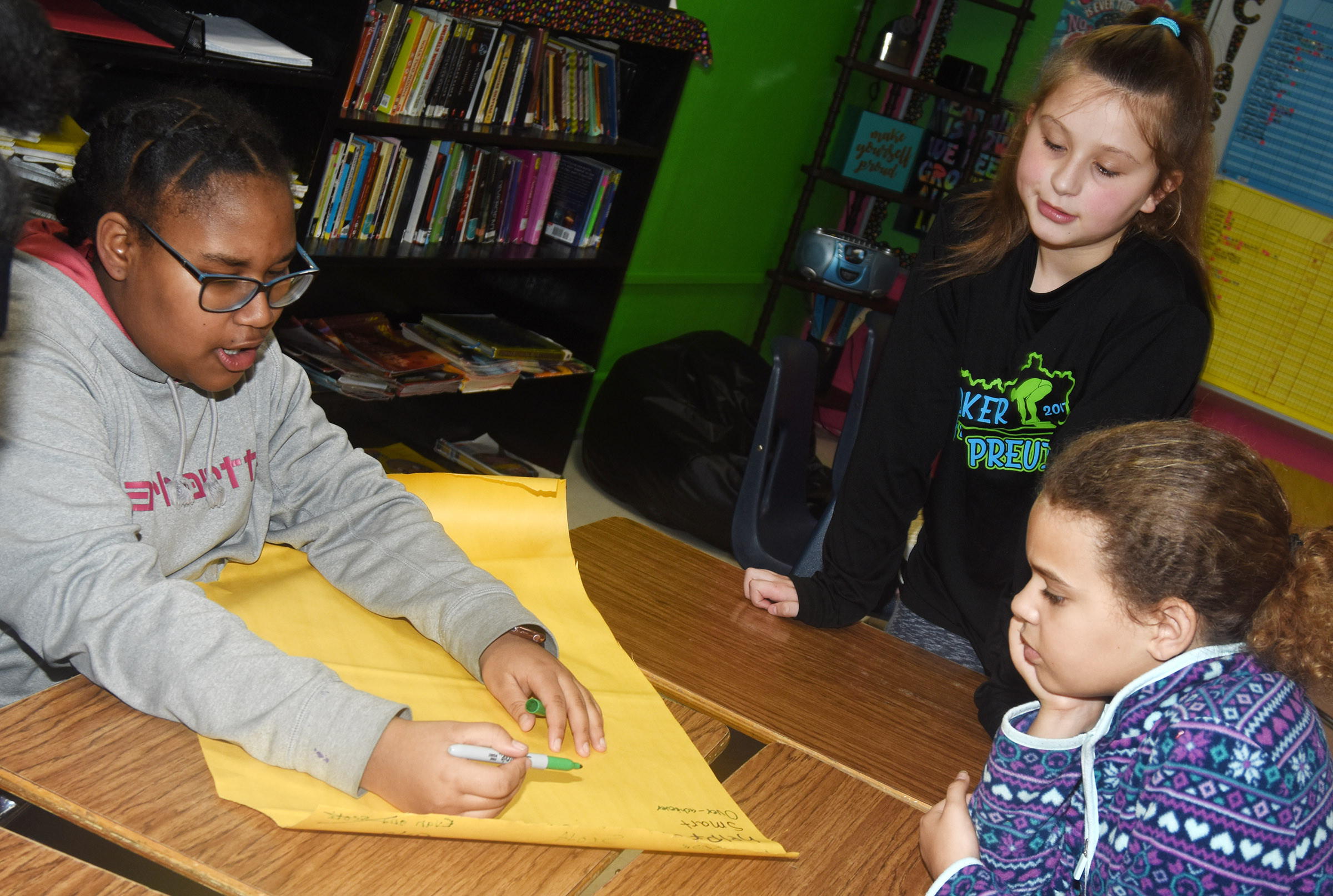 CMS sixth-graders, from left, KyAshia Mitchell, Mollie Bailey and Arisha Francis work together in a reading session.