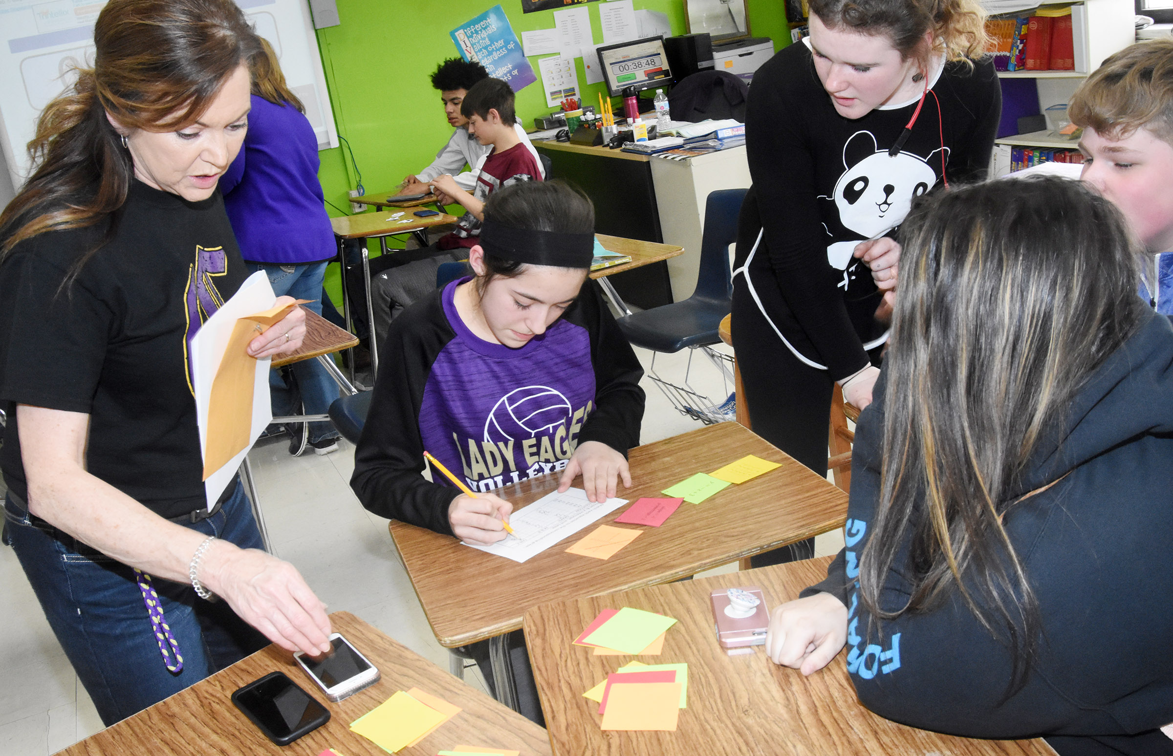 CMS eighth-grader teacher Melisa Morris helps her students as they compete in the Escape room challenge.