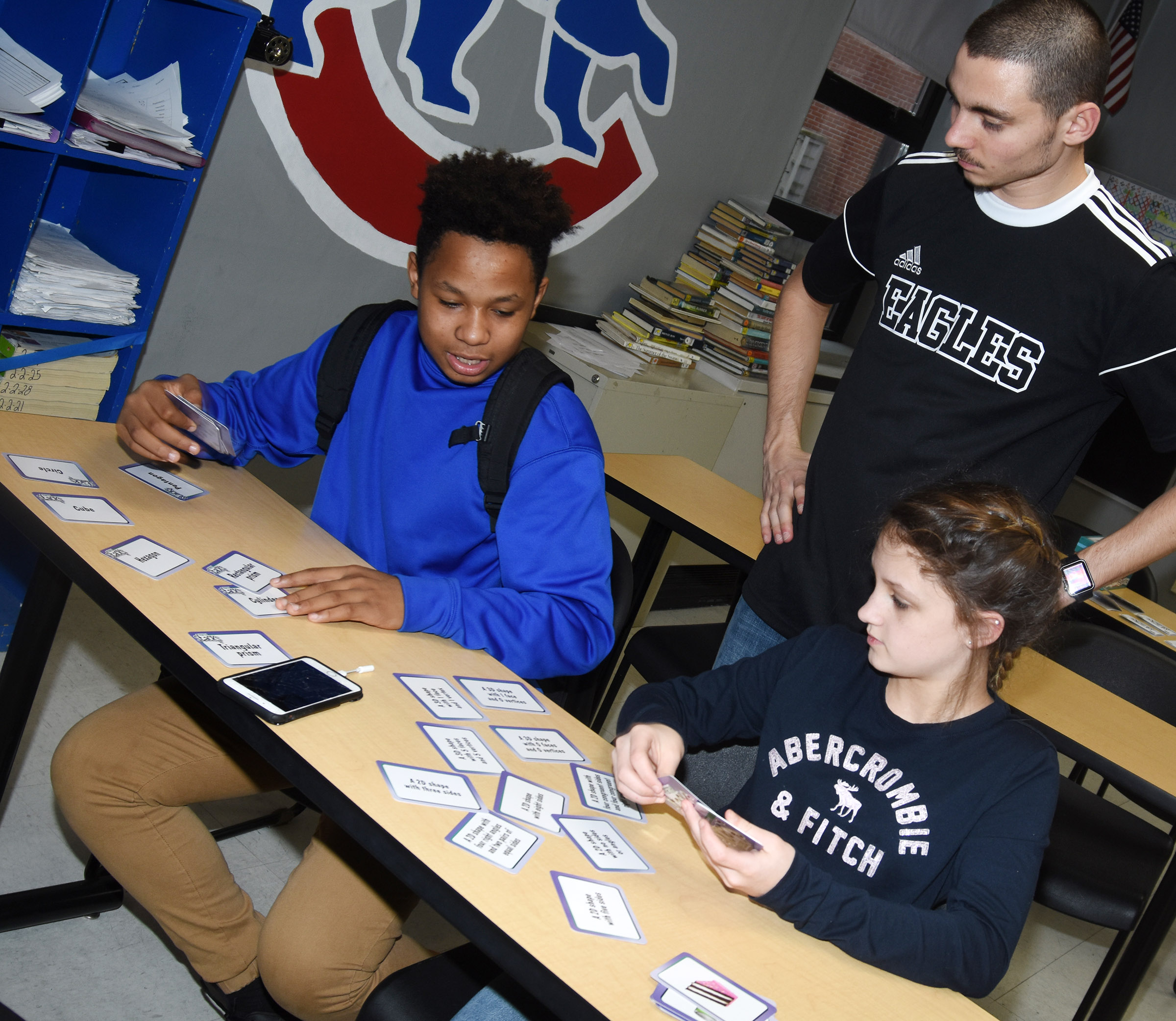 CMS math teacher Bradley Harris helps seventh-graders Deondre' Weathers, at left, and Alexis Byers as they play a math flashcard game.