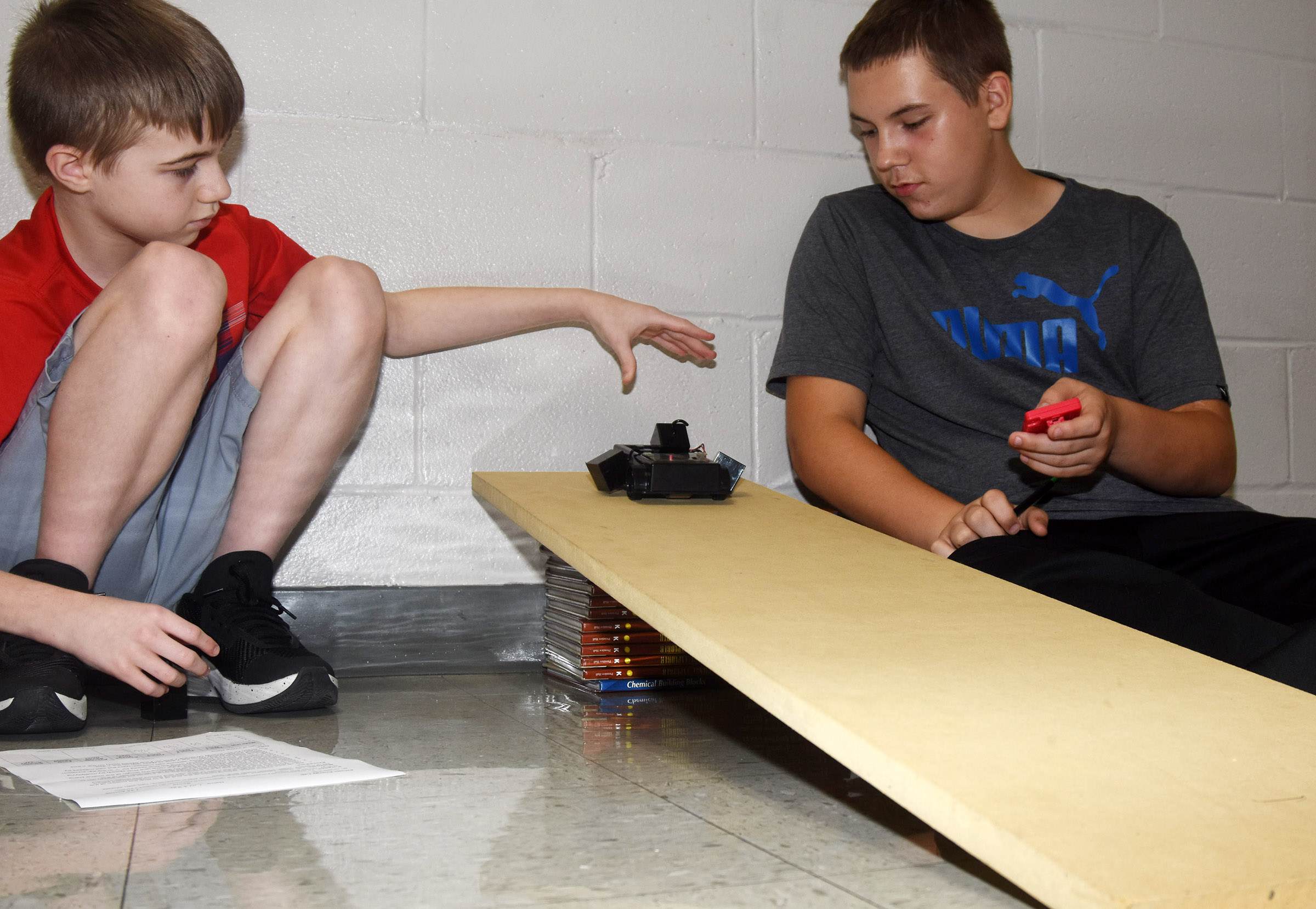 CES seventh-graders Ethan Cox, at left, and Isaac Roddy test their car.