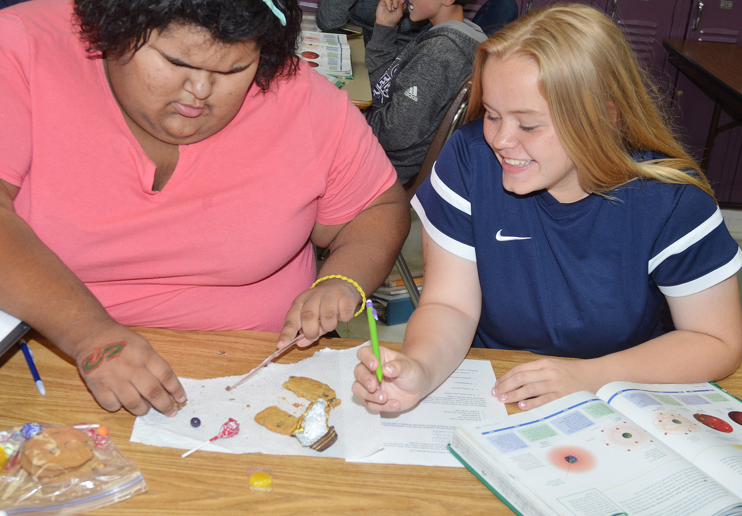 CMS eighth-grader Tynisha Richerson, at left, and Campbellsville High School freshman Riley Rainwater compare their candies to the atomic models.