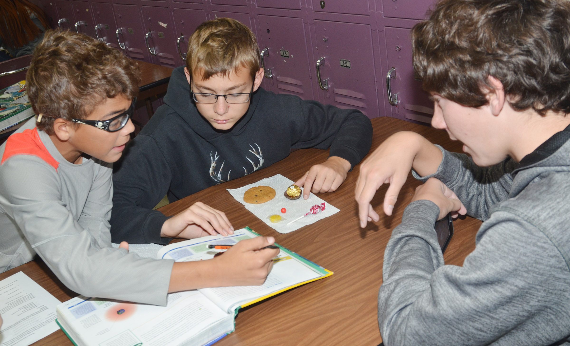 From left, CMS eighth-graders Logan Phillips, Jarred Mays and Peyton Dabney compare their candies to the atomic models.