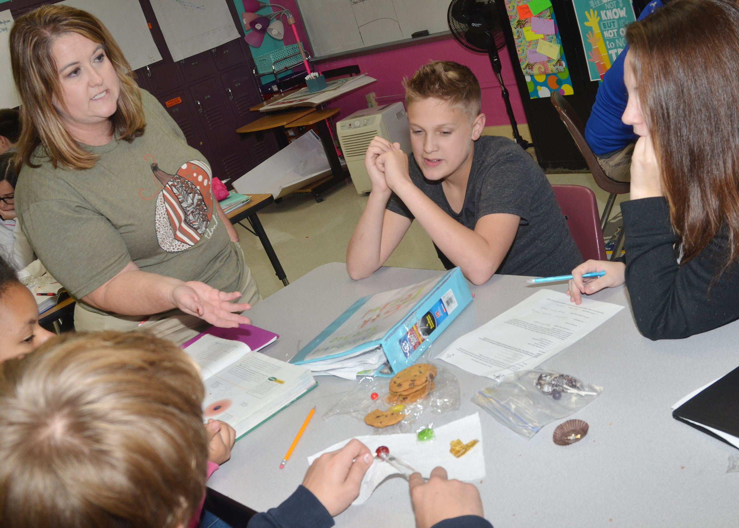 CMS science teacher Amy Knifley talks to eighth-grader Jayden Murphy and his groupmates about their atomic models.