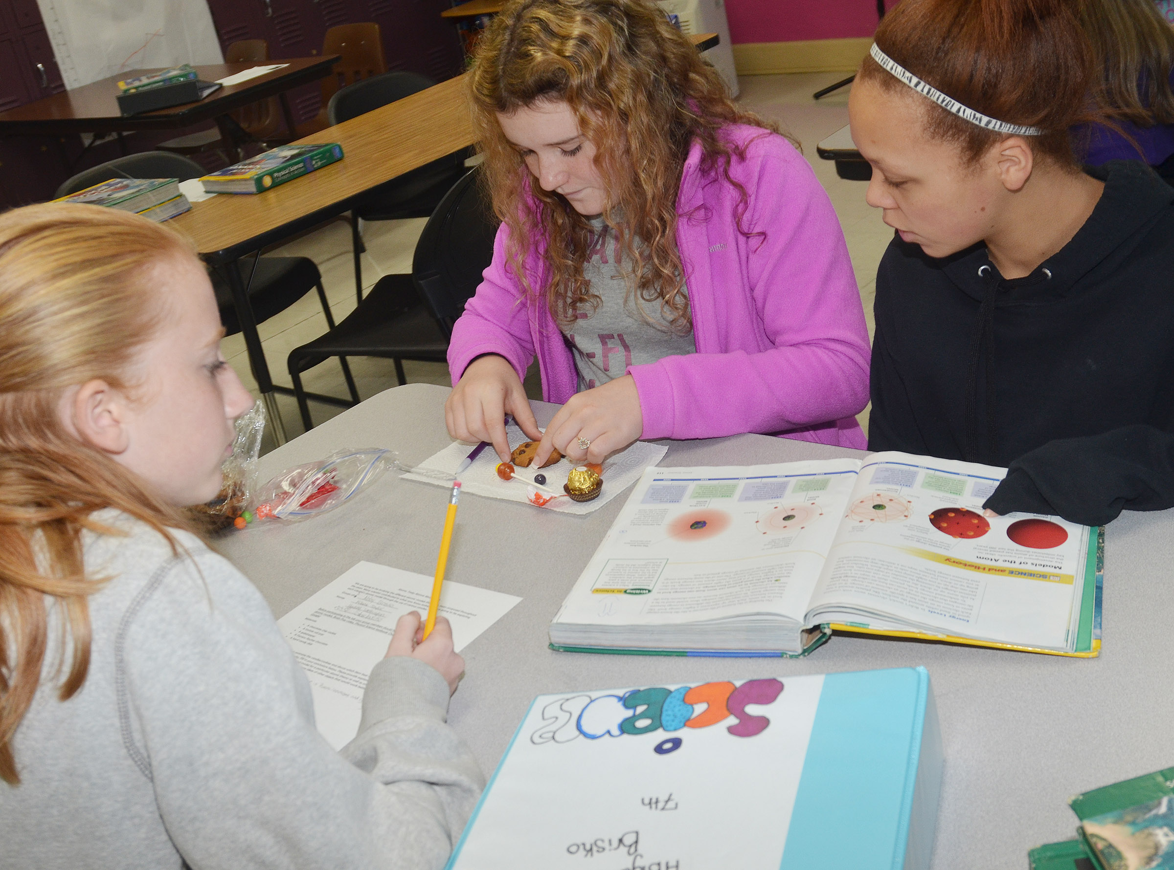 From left, CMS eighth-graders Hayley Wethington, Abigail Brisko and Kitana Taylor compare their candies to the atomic models.