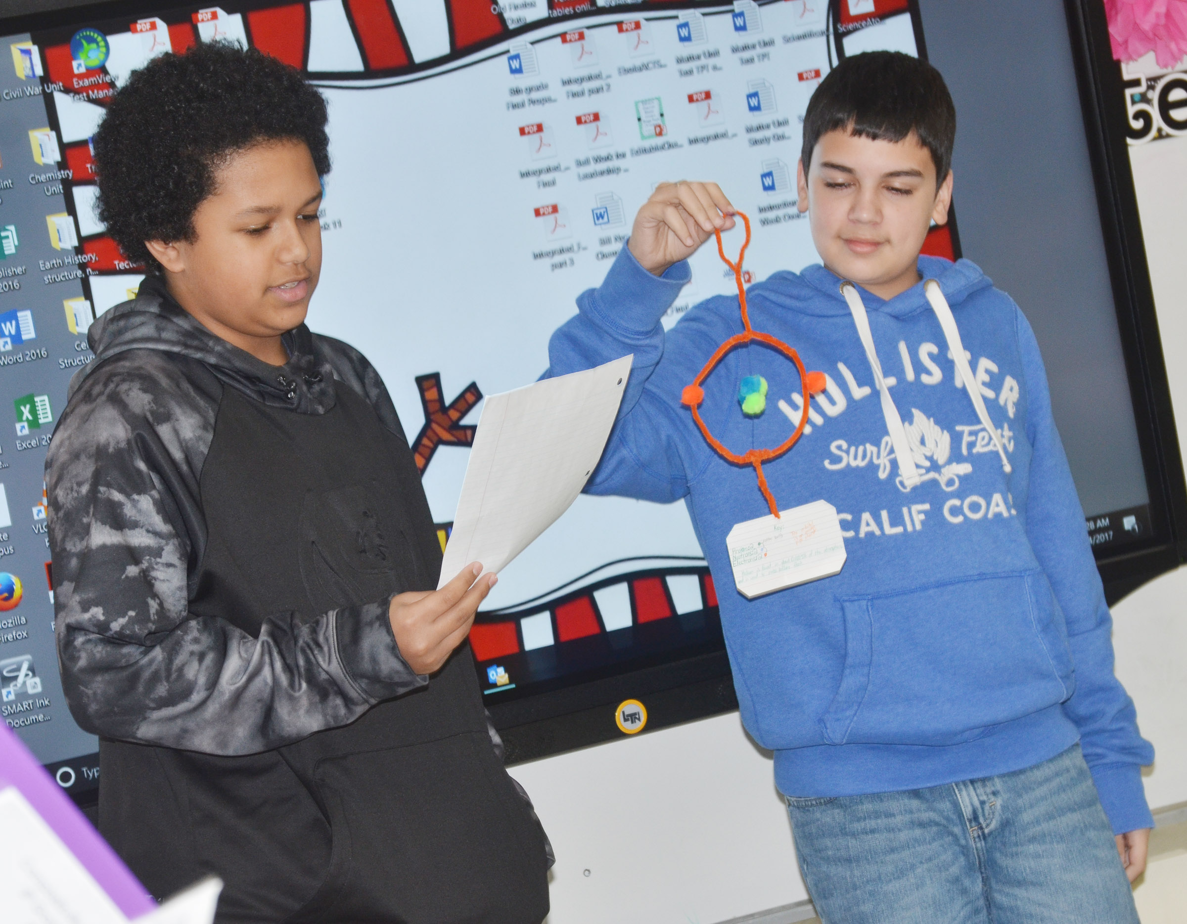 CMS eighth-grader Tezon Mitchell, at left, presents about Helium as classmate Jaylin Napier holds his model.