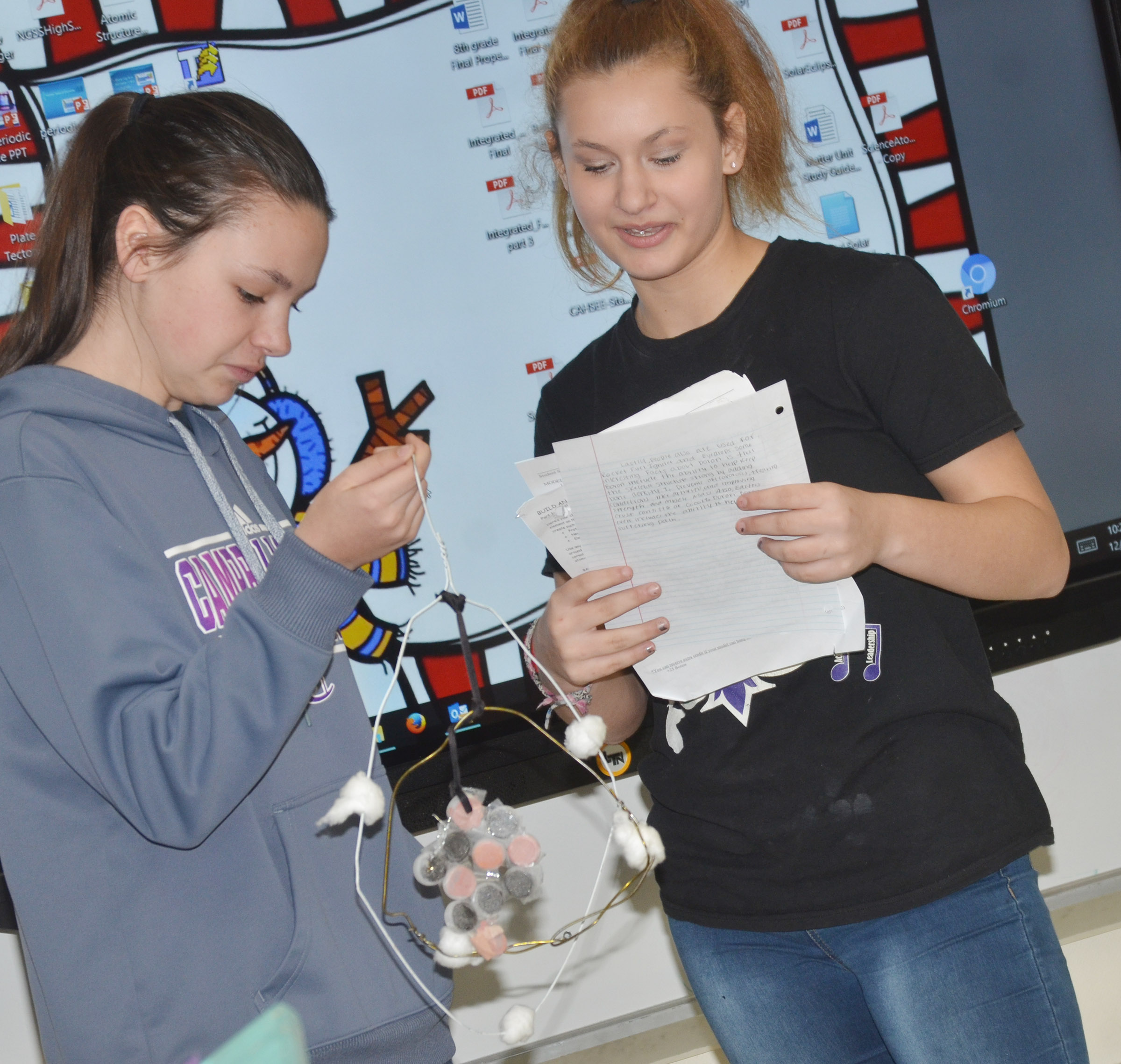 CMS eighth-grader Christina Miller, at right, talks about Boron as classmate Karley Morris holds her model.