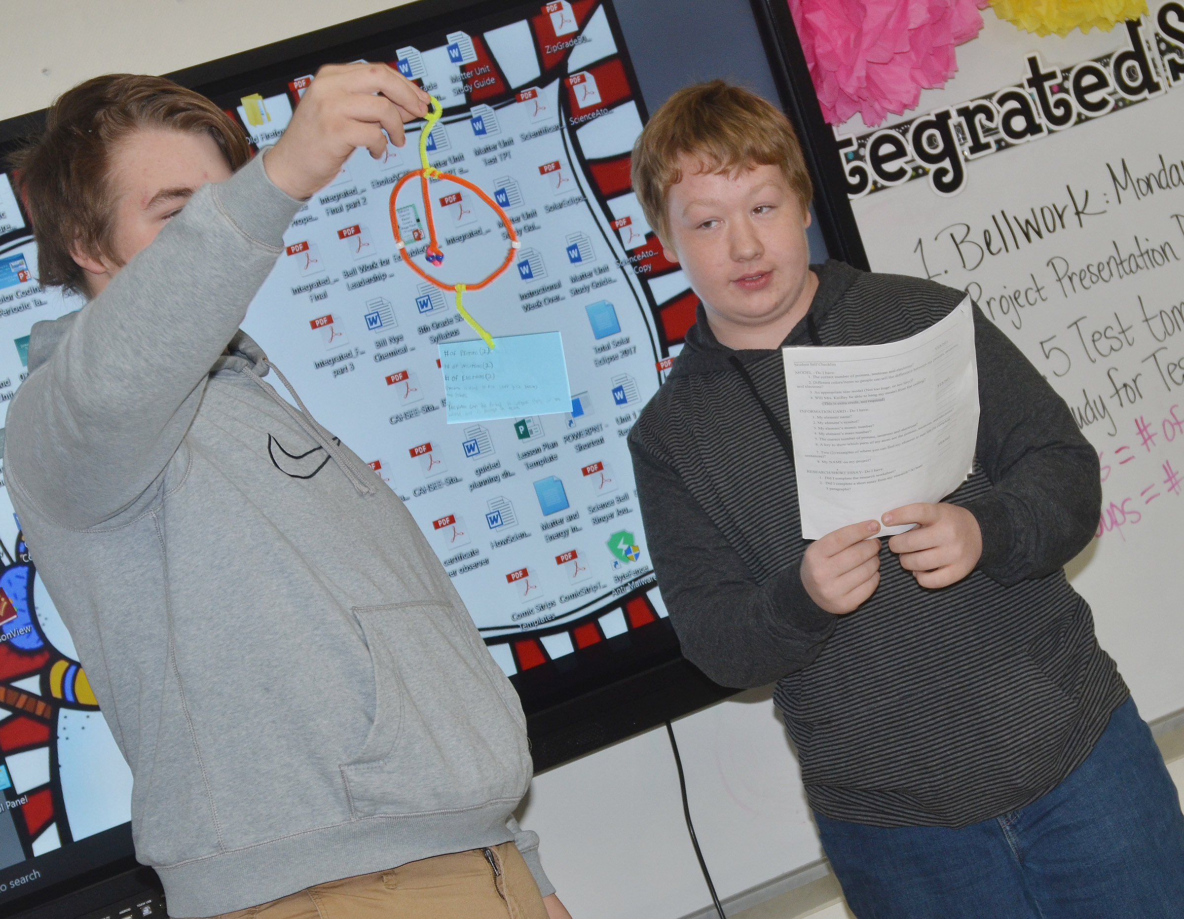 CMS eighth-grader Ryan Milburn, at right, talks about Helium as classmate Austin Jeffries holds his model.