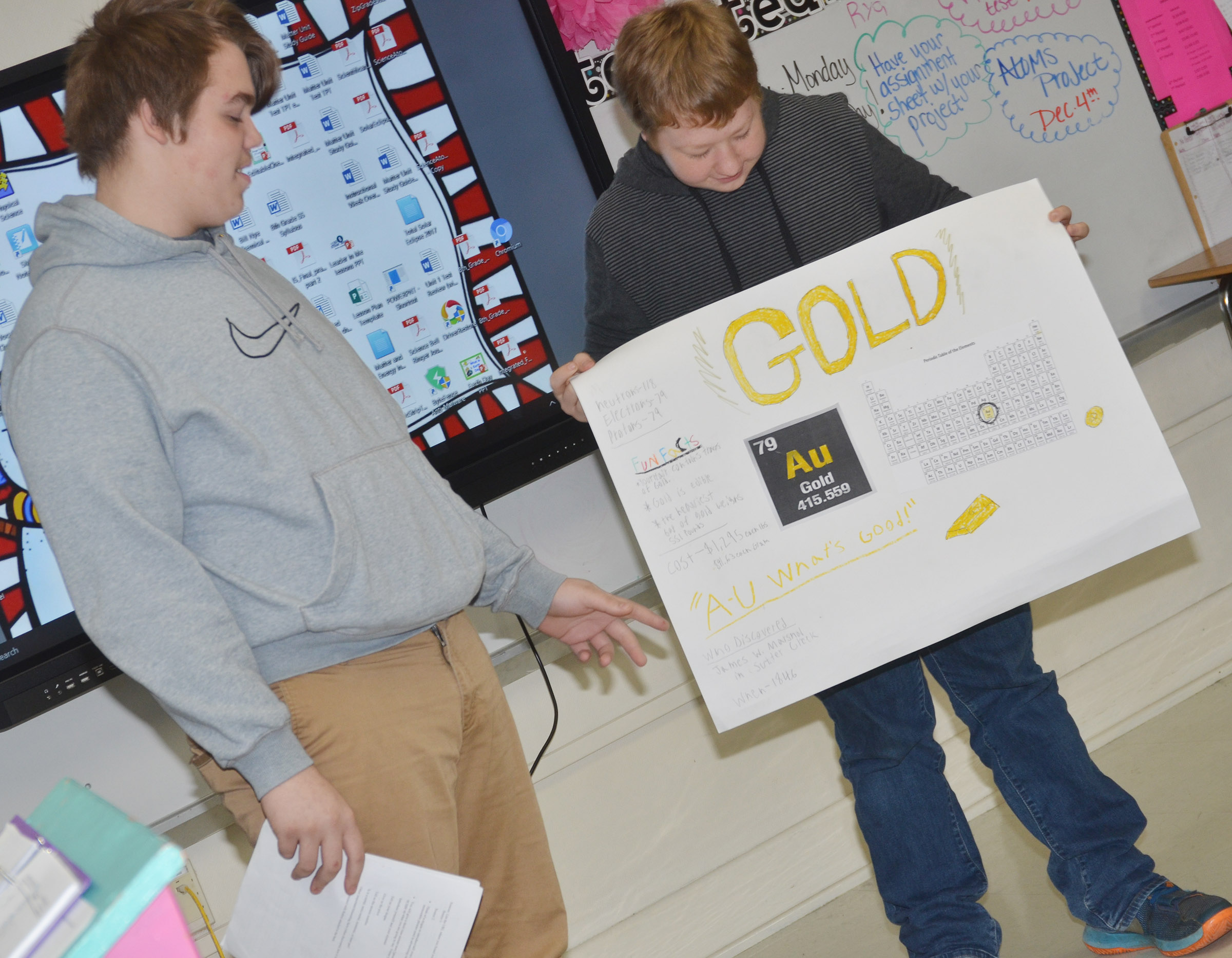 CMS eighth-grader Austin Jeffries, at left, talks about Gold as classmate Ryan Milburn holds his poster.