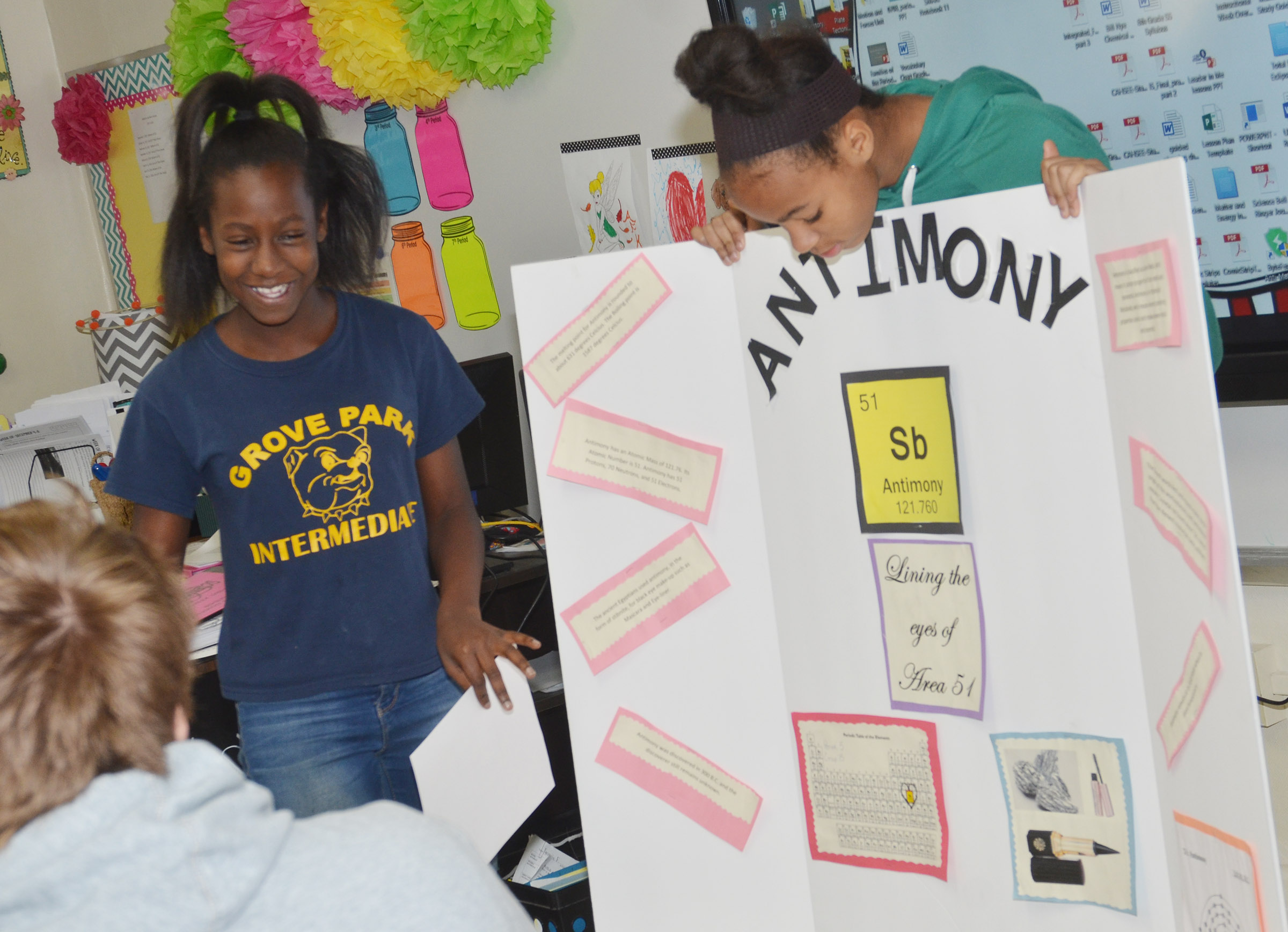 CMS eighth-grader Myricle Gholston, at left, talks about Antimony as classmate Aun Daya Coleman holds her poster.