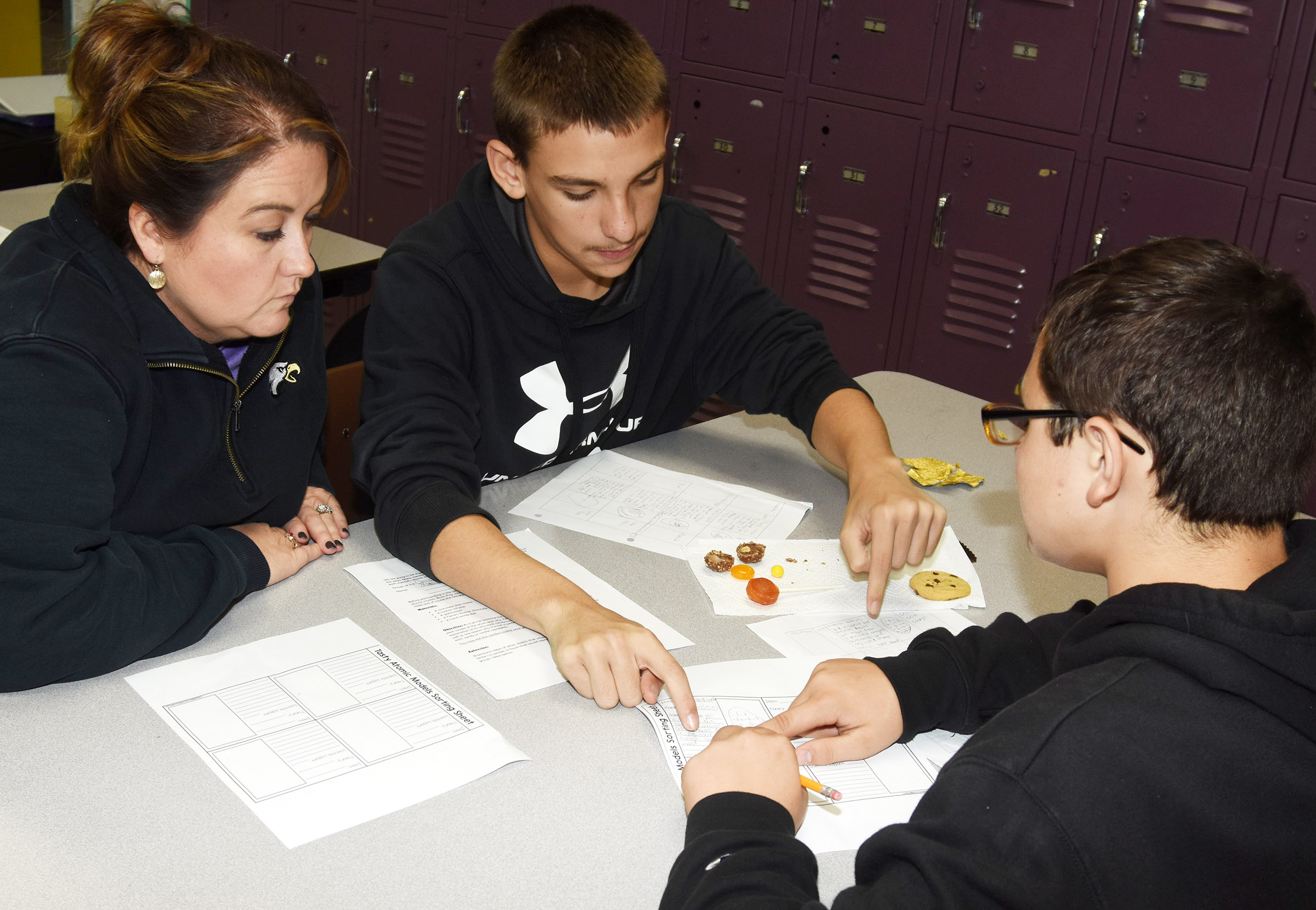 CMS teacher Amy Knifley talks to eighth-graders Nate Mitchell, at left, and Cameron Mahan about how the candies are similar to the atomic models.