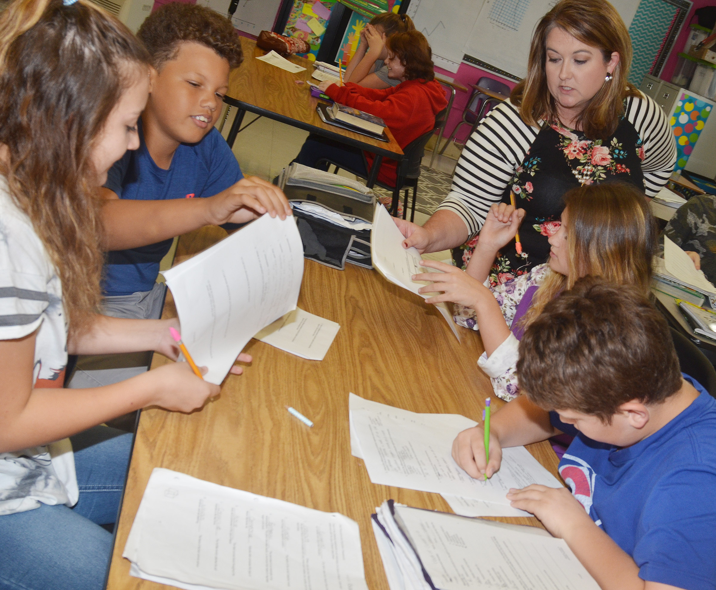 CMS science teacher Amy Knifley helps, from left, seventh-graders Briana Davis, Amare Poynter, Alexis Byers and Weston Mattingly with their study guide.