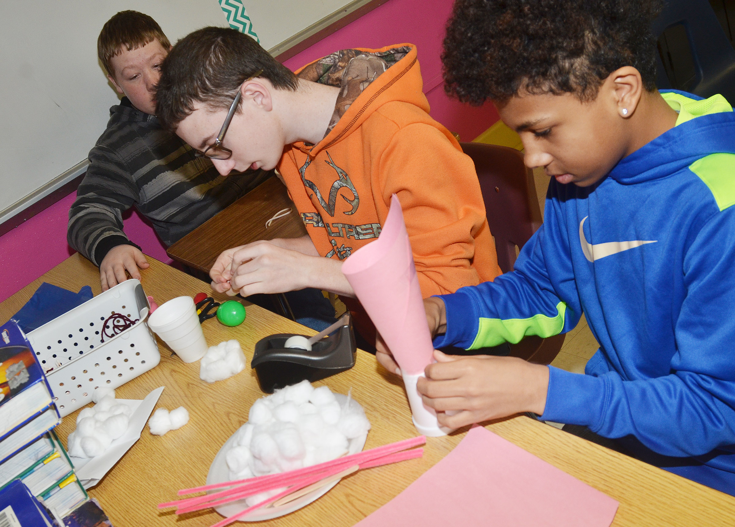 From left, CMS eighth-graders Ryan Milburn, Jonathan Sparks and Lorenzo Coulter build their egg dropper containers.