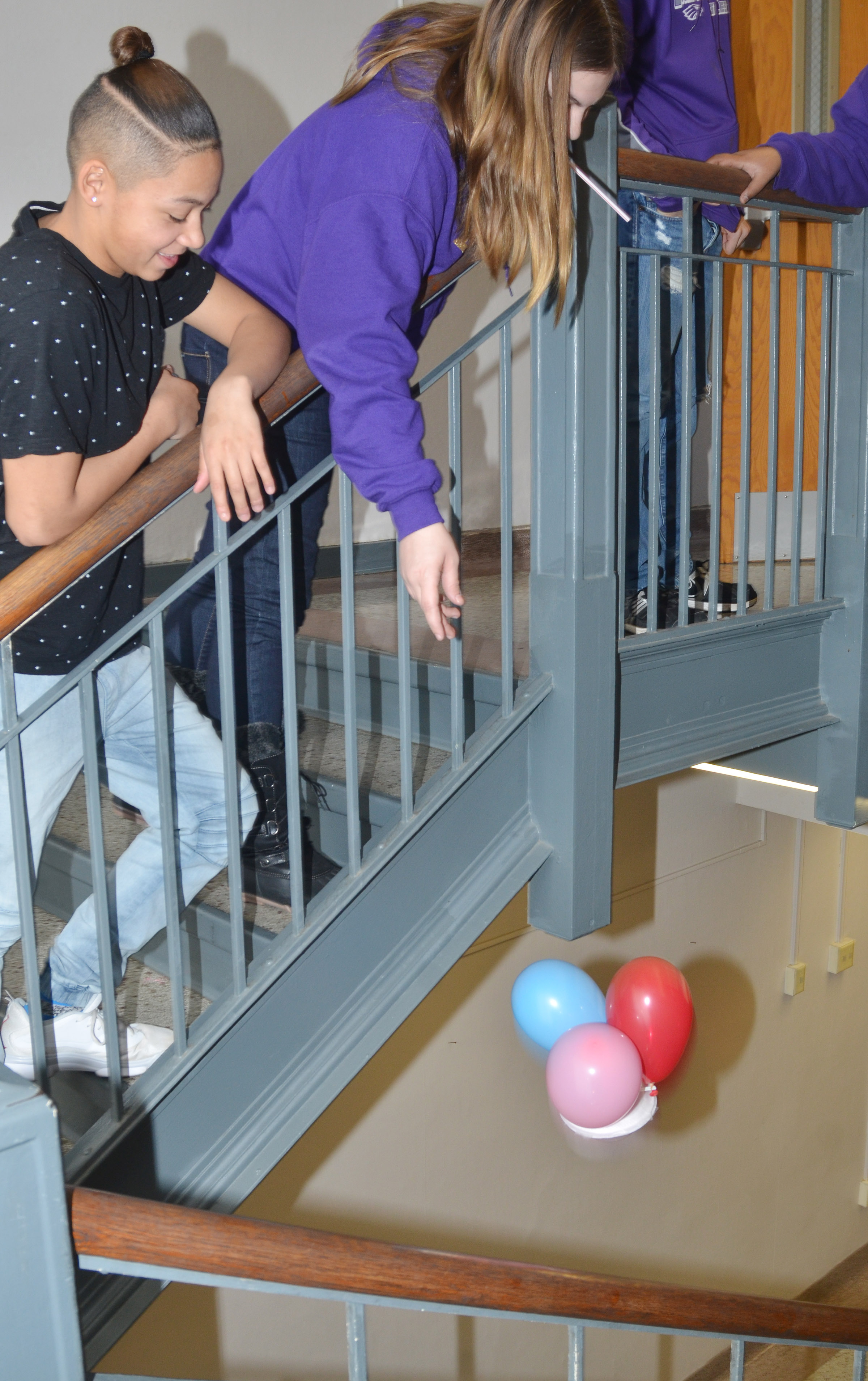 CMS eighth-grader Samantha Underwood drops the egg dropper container she built with classmate Taylor Whaley, at left.