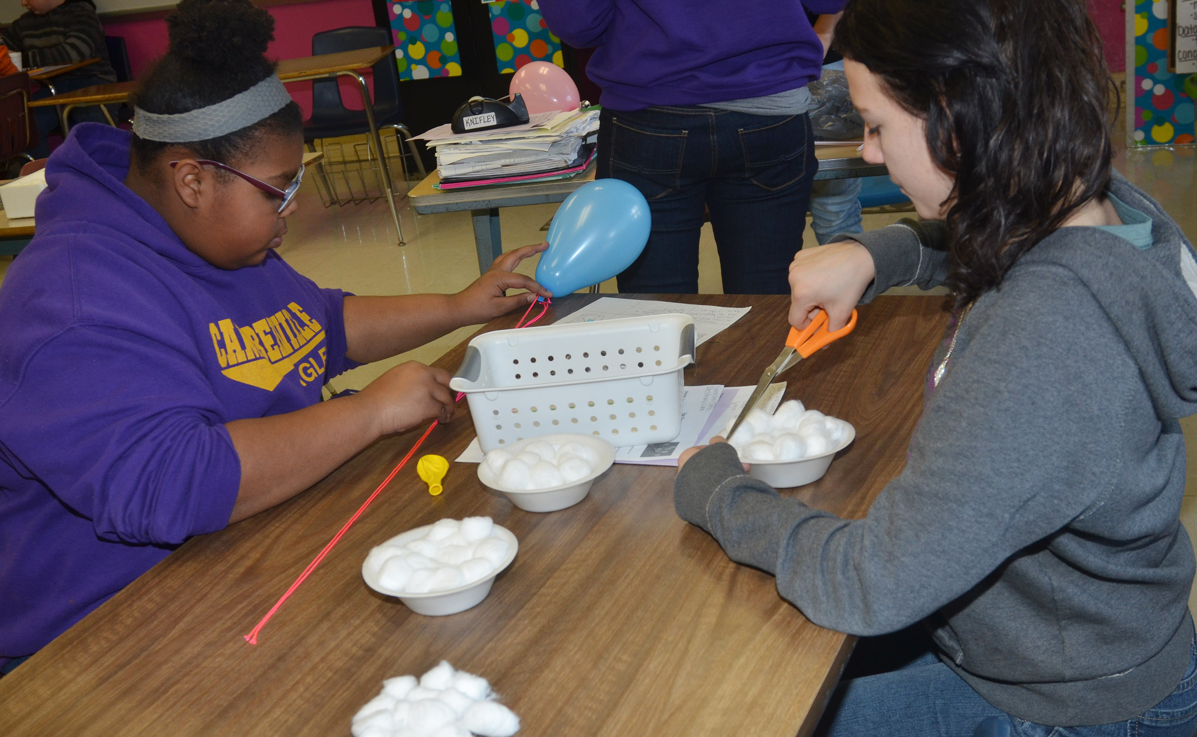 CMS eighth-graders Destany Lane, at left, and Natasha Combs build their egg dropper container.