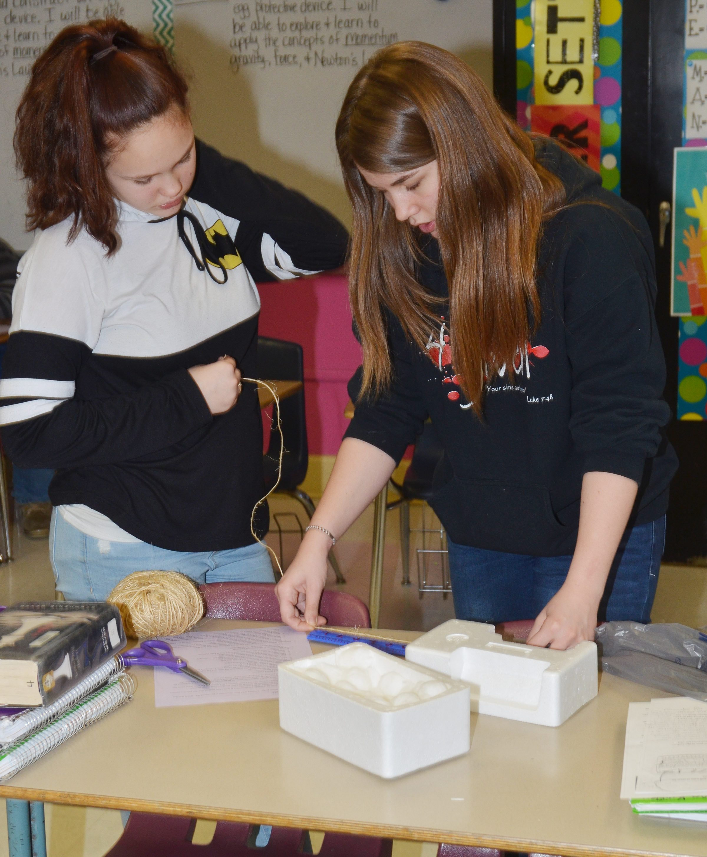 CMS eighth-graders Mystique Jones, at left, and MaKala Hammett build their egg dropper container.