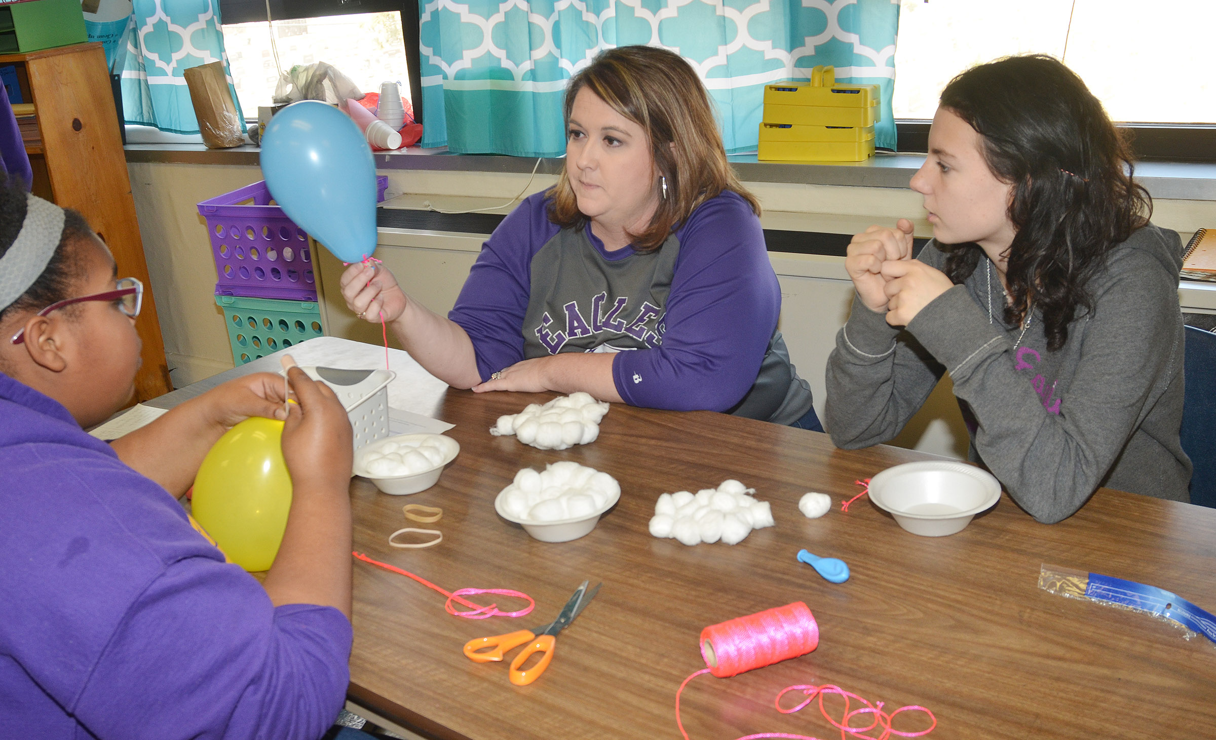 CMS teacher Amy Knifley talks to eighth-graders Destany Lane, at left, and Natasha Combs about their egg dropper container.