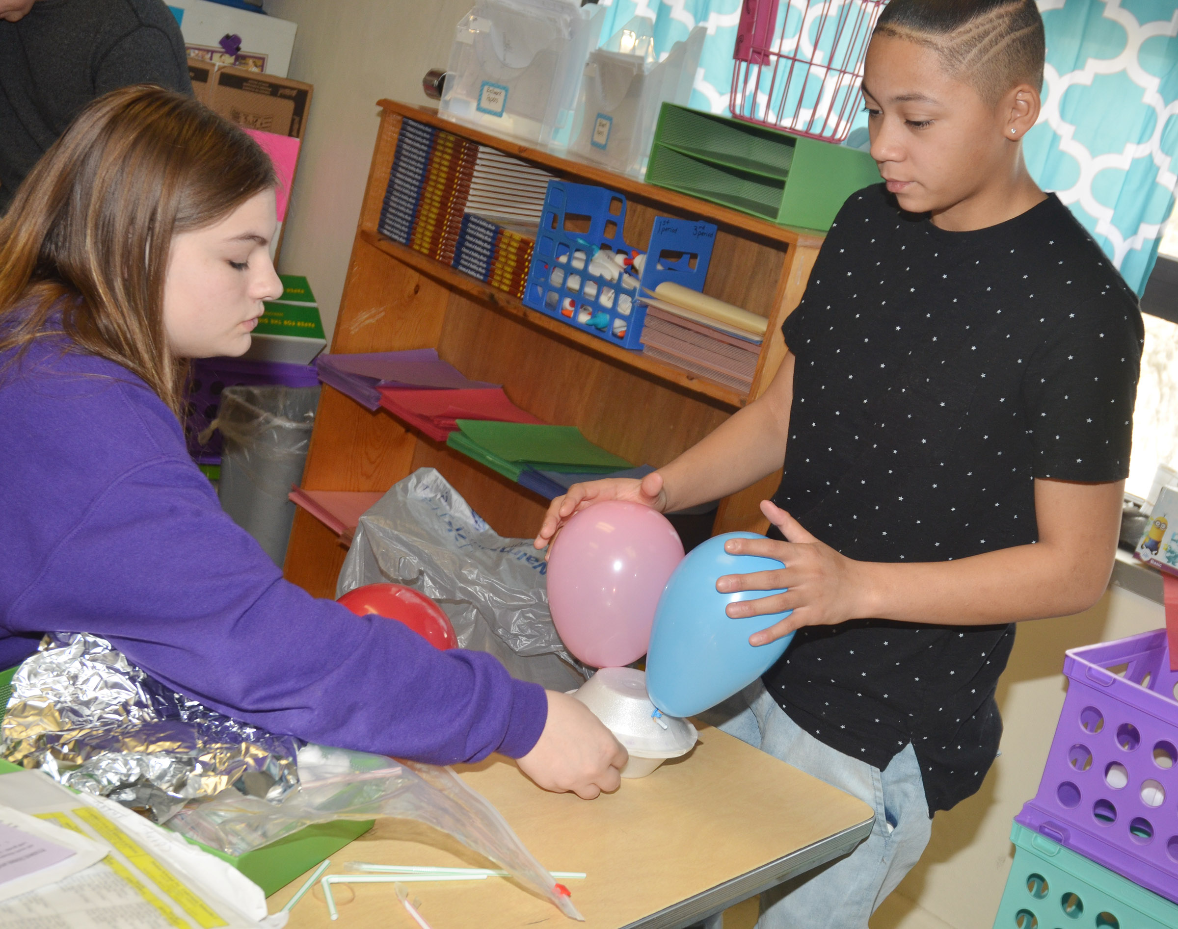 CMS eighth-graders Samantha Underwood, at left, and Taylor Whaley build their egg dropper container.
