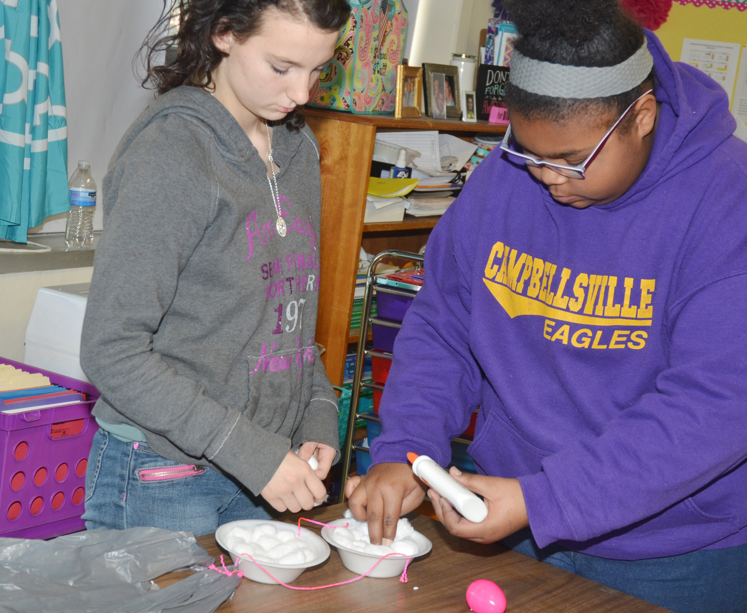 CMS eighth-graders Natasha Combs, at left, and Destany Lane build their egg dropper container.